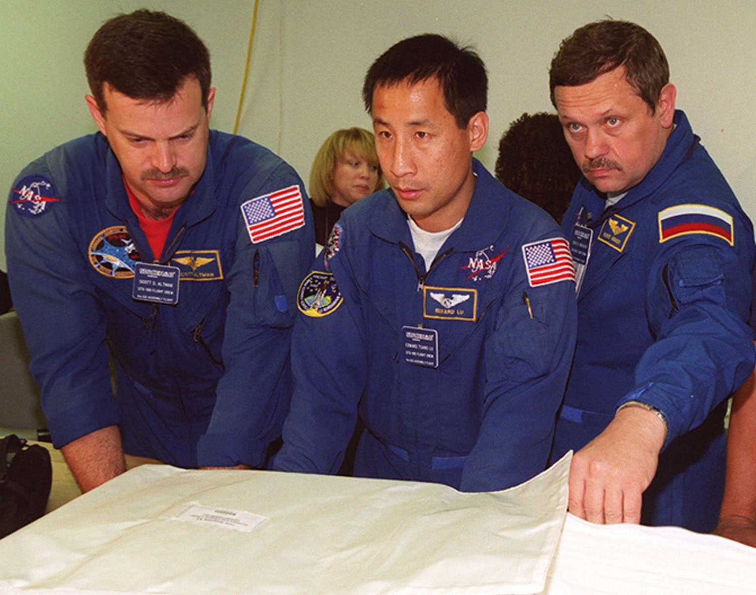 KENNEDY SPACE CENTER, FLA. -- At SPACEHAB, Port Canaveral, Fla., members of the STS-106 crew become familiar with part of the payload on their mission to the International Space Station. From left are Pilot Scott Altman and Mission Specialists Edward Lu and Boris Morukov, who is with the Russian Space Agency. Among the payload is the Treadmill Vibration Isolation System (TVIS), a device to collect data on how vibrations imparted by crew exercise may be reduced or eliminated on the International Space Station. Those vibrations could disturb delicate microgravity experiments on the Space Station. During the mission, the crew will complete service module support tasks on orbit, transfer supplies and outfit the Space Station for the first long-duration crew. STS-106 is scheduled to launch Sept. 8