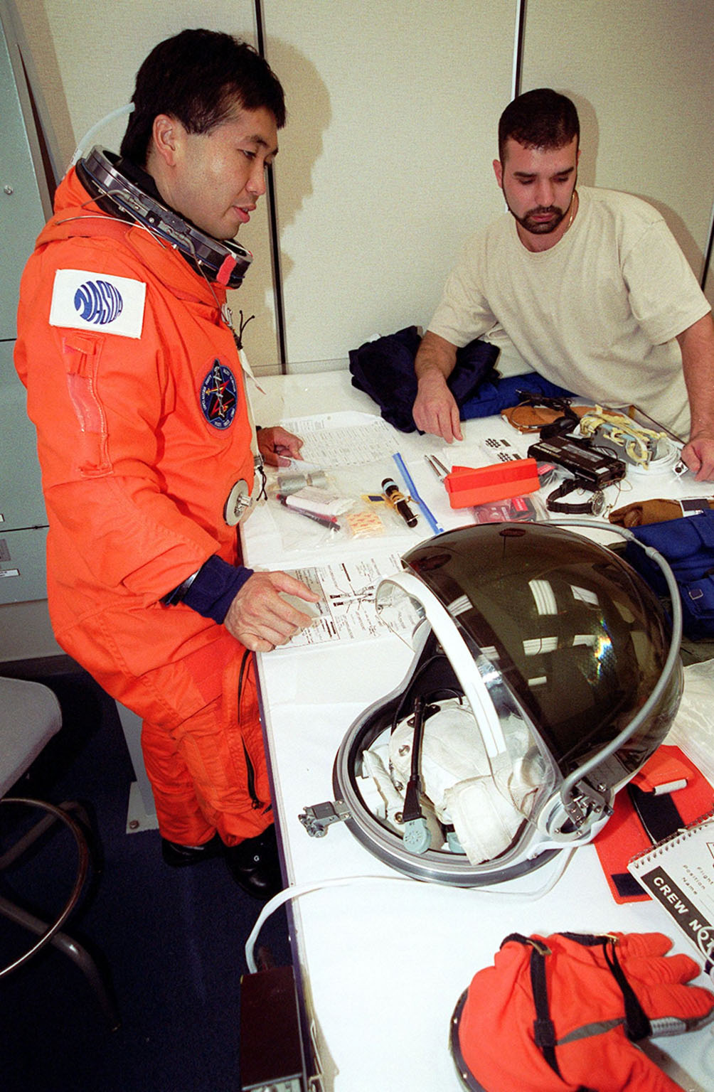 During pre-pack and fit check in the Operations and Checkout Building, STS-92 Mission Specialist Koichi Wakata of Japan looks over the equipment he will be wearing during launch and entry, such as the helmet and gloves on the table. Wakata and the rest of the crew are at KSC for Terminal Countdown Demonstration Test activities. The TCDT provides emergency egress training, simulated countdown exercises and opportunities to inspect the mission payload. This mission will be Wakata?s second Shuttle flight. STS-92 is scheduled to launch Oct. 5 at 9:38 p.m. EDT from Launch Pad 39A on the fifth flight to the International Space Station. It will carry two elements of the Space Station, the Integrated Truss Structure Z1 and the third Pressurized Mating Adapter. The mission is also the 100th flight in the Shuttle program