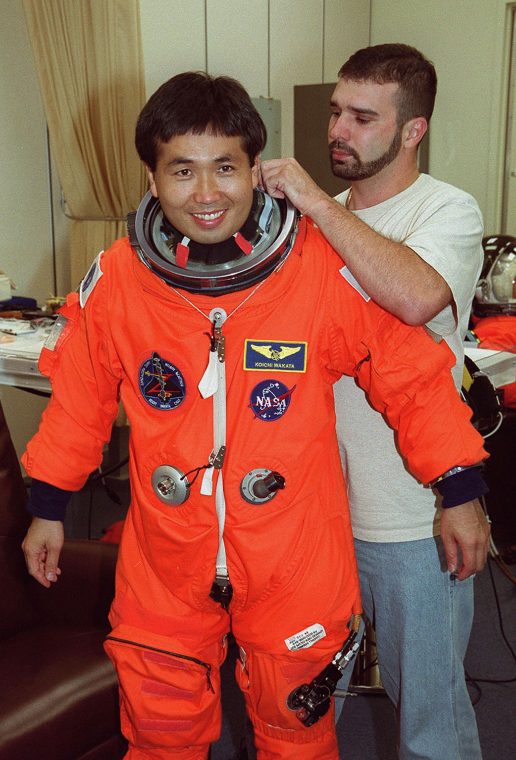During pre-pack and fit check in the Operations and Checkout Building, STS-92 Mission Specialist Koichi Wakata of Japan gets an adjustment on his launch and entry suit. This mission is Wakata?s second Shuttle flight. He and the rest of the crew are at KSC for Terminal Countdown Demonstration Test activities. The TCDT provides emergency egress training, simulated countdown exercises and opportunities to inspect the mission payload. STS-92 is scheduled to launch Oct. 5 at 9:38 p.m. EDT from Launch Pad 39A on the fifth flight to the International Space Station. It will carry two elements of the Space Station, the Integrated Truss Structure Z1 and the third Pressurized Mating Adapter. The mission is also the 100th flight in the Shuttle program