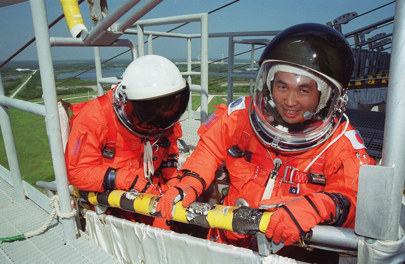 KENNEDY SPACE CENTER, FLA. -- On the 195-foot level of the Fixed Service Structure on Launch Pad 39A, STS-92 Mission Specialists William S. McArthur Jr. (left) and Koichi Wakata of Japan test the slidewire basket that they are in. They and other crew members are taking part in emergency egress training, one of the Terminal Countdown Demonstration Test activities that also include a simulated countdown. STS-92 is scheduled to launch Oct. 5 at 9:38 p.m. EDT on the fifth flight to the International Space Station. It will carry two elements of the Space Station, the Integrated Truss Structure Z1 and the third Pressurized Mating Adapter. The mission is also the 100th flight in the Shuttle program