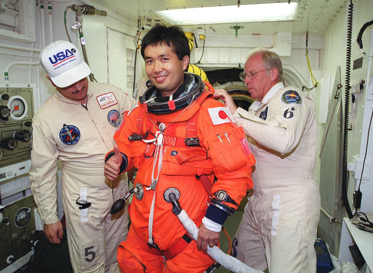 STS-92 Mission Specialist Koichi Wakata of Japan (center) gets help from United Space Alliance Mechanical Technician Vinny Difranzo (left) and NASA Quality Assurance Specialist Danny Wyatt (right) in suiting up in the White Room. Wakata and other crew members are taking part in a simulated countdown KSC for Terminal Countdown Demonstration Test (TCDT) activities. STS-92 is scheduled to launch Oct. 5 at 9:38 p.m. EDT on the fifth flight to the International Space Station. It will carry two elements of the Space Station, the Integrated Truss Structure Z1 and the third Pressurized Mating Adapter. The mission is also the 100th flight in the Shuttle program