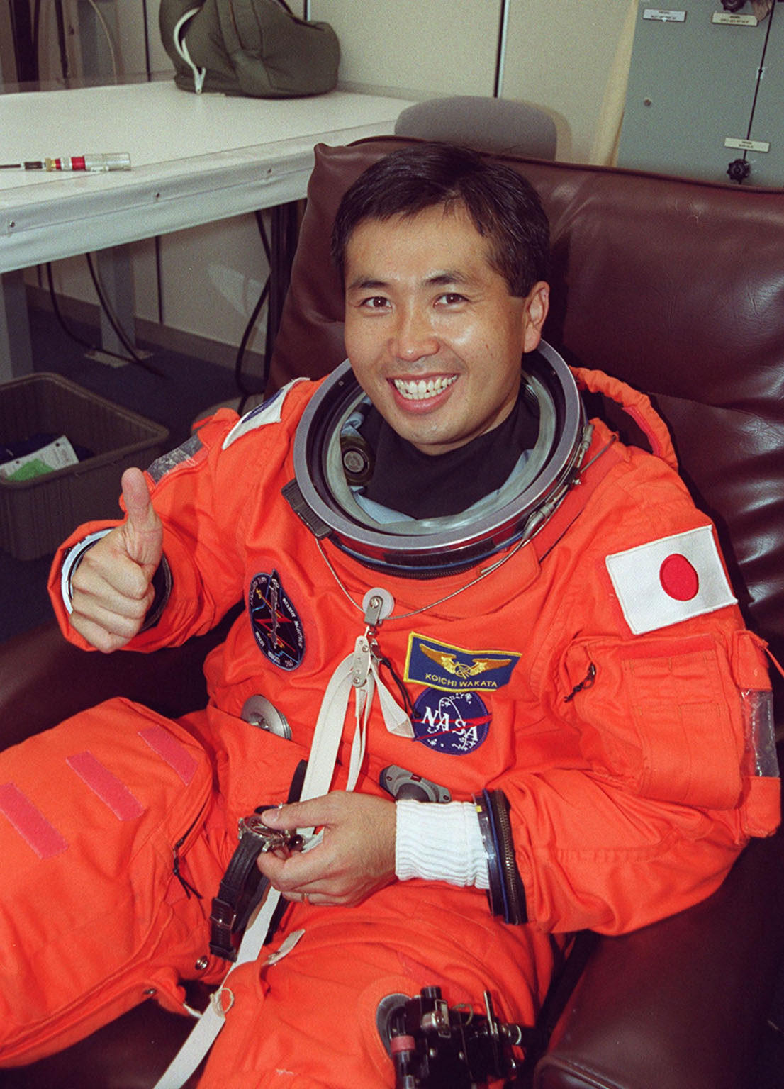 During suitup in the Operations and Checkout Building, STS-92 Mission Specialist Koichi Wakata of Japan signals thumbs up for a second launch attempt. During the 11-day mission to the International Space Station, four extravehicular activities (EVAs), or spacewalks, are planned for construction. The payload includes the Integrated Truss Structure Z-1 and the third Pressurized Mating Adapter. The Z-1 truss is the first of 10 that will become the backbone of the Space Station, eventually stretching the length of a football field. PMA-3 will provide a Shuttle docking port for solar array installation on the sixth Station flight and Lab installation on the seventh Station flight.; Launch is scheduled for 7:17 p.m. EDT. Landing is expected Oct. 22 at 2:10 p.m. EDT