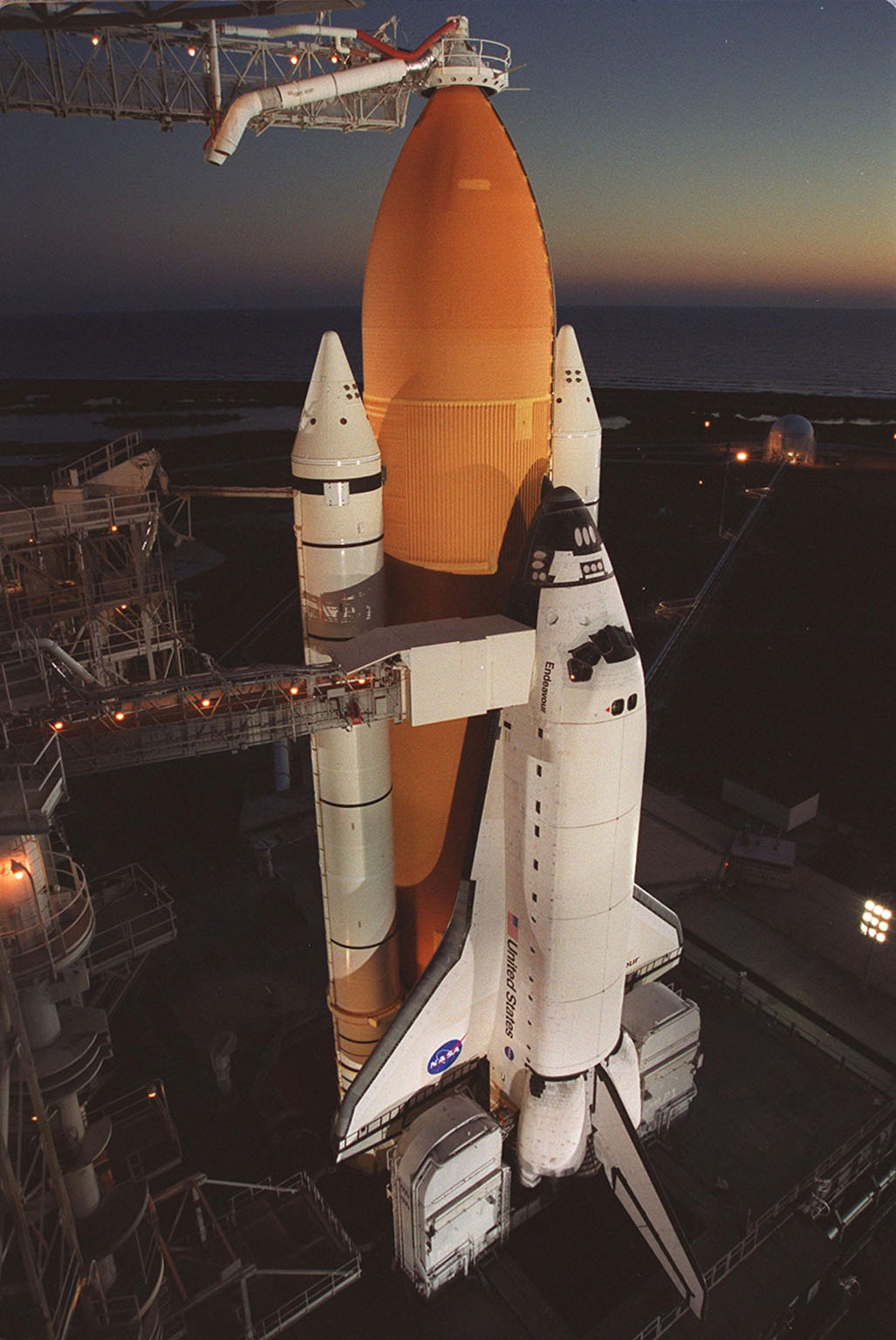 As dawn breaks on the horizon, Space Shuttle Endeavour is seen standing ready for launch, targeted for 10:06 p.m. EST tonight on mission STS-97 to the International Space Station. The Rotating Service Structure was rolled back just before dawn. On top of the orange external tank is the Gaseous Oxygen Vent Arm and its vent hood, known as the ?beanie cap.? The hood is raised to clear the external tank 2.5 minutes before launch. The orbiter carries the P6 Integrated Truss Segment containing solar arrays that will be temporarily installed to the Unity connecting module by the Z1 truss, recently delivered to and installed on the Station on mission STS-92. The two solar arrays are each more than 100 feet long. They will capture energy from the sun and convert it to power for the Station. Two spacewalks will be required to install the solar array connections