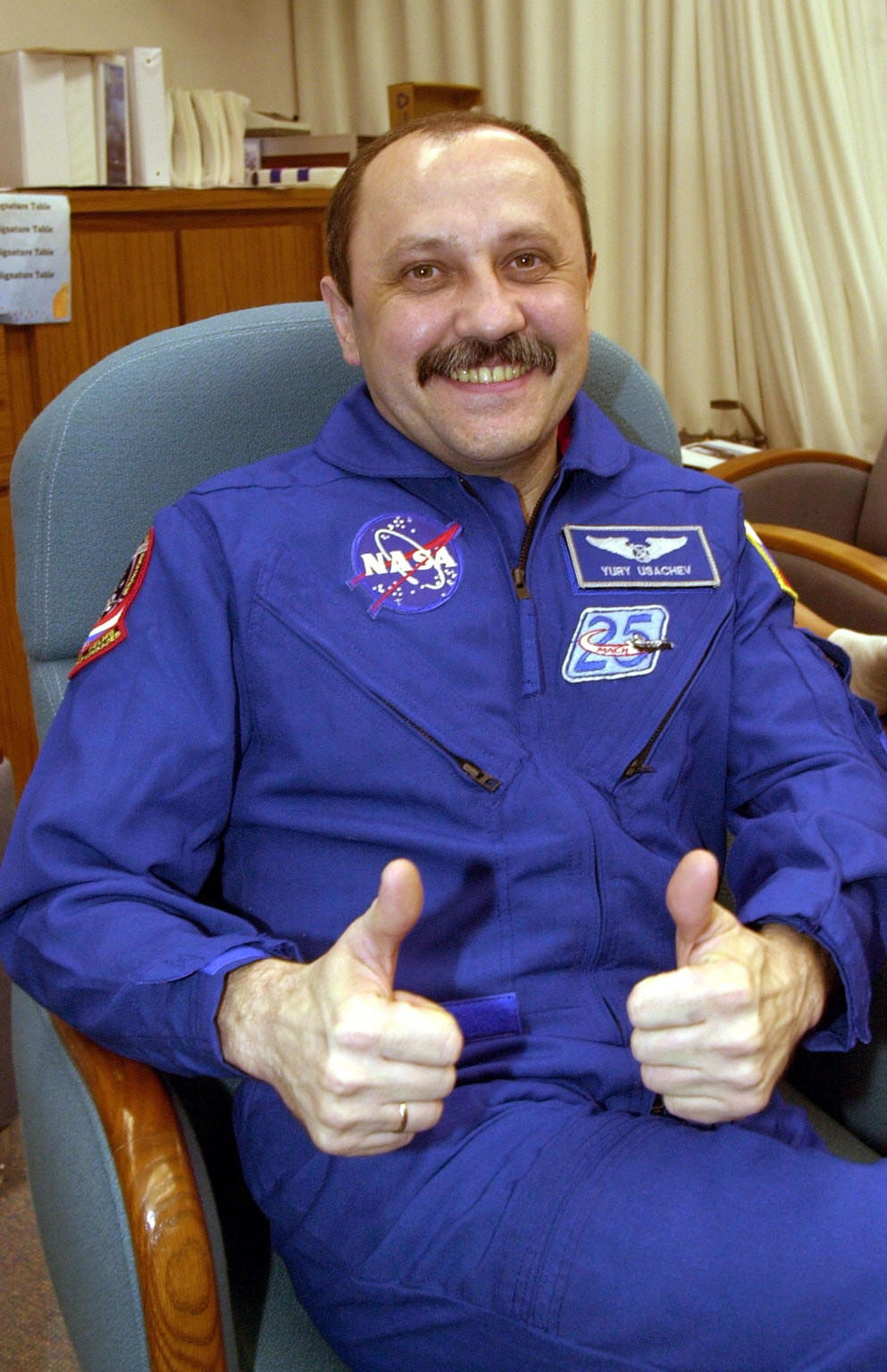 Expedition Two crew Commander Yury Usachev gives a thumbs up from the crew quarters in the Operations and Checkout Building following his return to Earth with the STS-105 crew aboard the orbiter Discovery. The Expedition Two crew have spent the past five months living and working on the International Space Station. Mission STS-105 came to a close upon landing at KSC's Shuttle Landing Facility runway 15 after a 4.3-million-mile mission to the International Space Station. Main gear touchdown was at 2:22:58 p.m.EDT; wheel stop, at 2:24:06 p.m. EDT. The 11-day, 21-hour, 12-minute STS-105 mission accomplished the goals set for the 11th flight to the International Space Station: swapout of the resident Station crew; delivery of equipment, supplies and scientific experiments; and installation of the Early Ammonia Servicer and heater cables for the S0 truss on the Station. Discovery completed its 30th flight into space, the 106th mission of the Space Shuttle program. Out of five missions in 2001, the landing was the first to occur in daylight at KSC