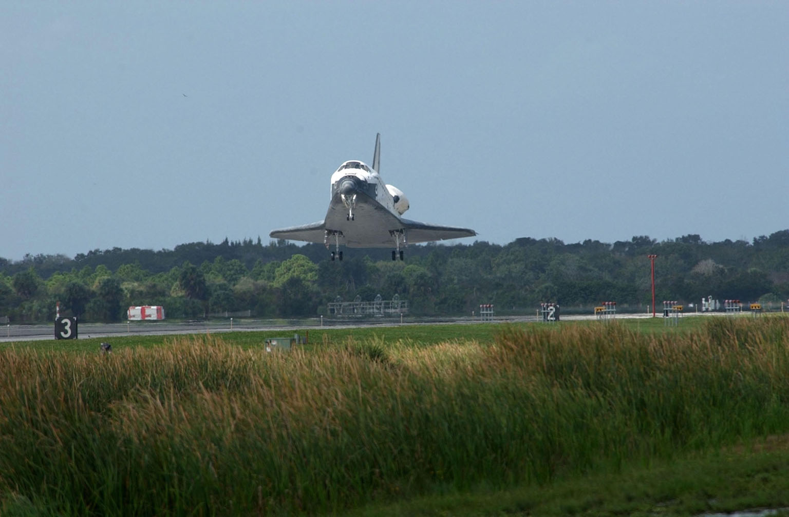 KENNEDY SPACE CENTER, FLA. -- Orbiter Endeavour approaches Runway 15 at the KSC Shuttle Landing Facility, after a mission elapsed time of 11 days, 19 hours, 35 minutes. Main gear touchdown occurred at 12:55:10 p.m. EST, nose gear touchdown at 12:55:23 p.m. , wheel stop at 12:56:13 p.m. The landing, the 57th at KSC in the history of the program, completed the STS-108 mission known as Utilization Flight 1, which was the 12th mission to the International Space Station. This mission was the 107th flight in the Shuttle program and the 17th flight for the orbiter. Endeavour carries both the mission crew and the Expedition 3 crew - Commander Frank Culbertson and cosmonauts Vladimir Dezhurov and Mikhail Tyurin - who are returning to Earth after 129 days in space on the Space Station