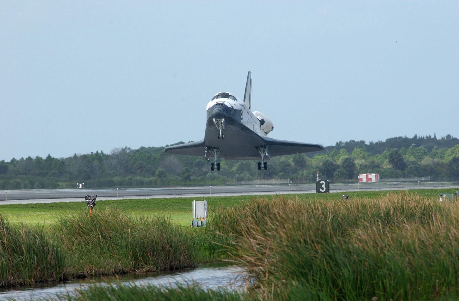 KENNEDY SPACE CENTER, FLA. - After dropping through cloud cover, Orbiter Endeavour approaches Runway 15 at the KSC Shuttle Landing Facility, with a mission elapsed time of 11 days, 19 hours, 35 minutes. Main gear touchdown occurred at 12:55:10 p.m. EST, nose gear touchdown at 12:55:23 p.m. , wheel stop at 12:56:13 p.m. The landing, the 57th at KSC in the history of the program completed the STS-108 mission known as Utilization Flight 1, which was the 12th mission to the International Space Station. This mission was the 107th flight in the Shuttle program and the 17th flight for the orbiter. Endeavour carries both the mission crew and the Expedition 3 crew - Commander Frank Culbertson and cosmonauts Vladimir Dezhurov and Mikhail Tyurin - who are returning to Earth after 129 days in space on the Space Station