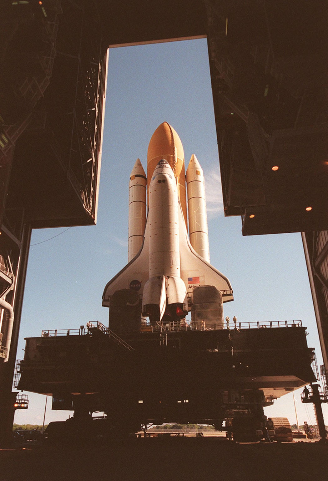 KENNEDY SPACE CENTER, Fla. -- Space Shuttle Atlantis inches its way out the doors of the Vehicle Assembly Building as it begins rolling out to Launch Pad 39A for the second time. An attempt to roll out on Jan. 2 incurred a failed computer processor on the crawler transporter and the Shuttle was returned to the Vehicle Assembly Building using a secondary computer processor on the vehicle. Atlantis will fly on mission STS-98, the seventh construction flight to the International Space Station, carrying the U.S. Laboratory, named Destiny. The lab will have five system racks already installed inside the module. After delivery of electronics in the lab, electrically powered attitude control for Control Moment Gyroscopes will be activated. Atlantis is scheduled for launch no earlier than Jan. 19, 2001, with a crew of five