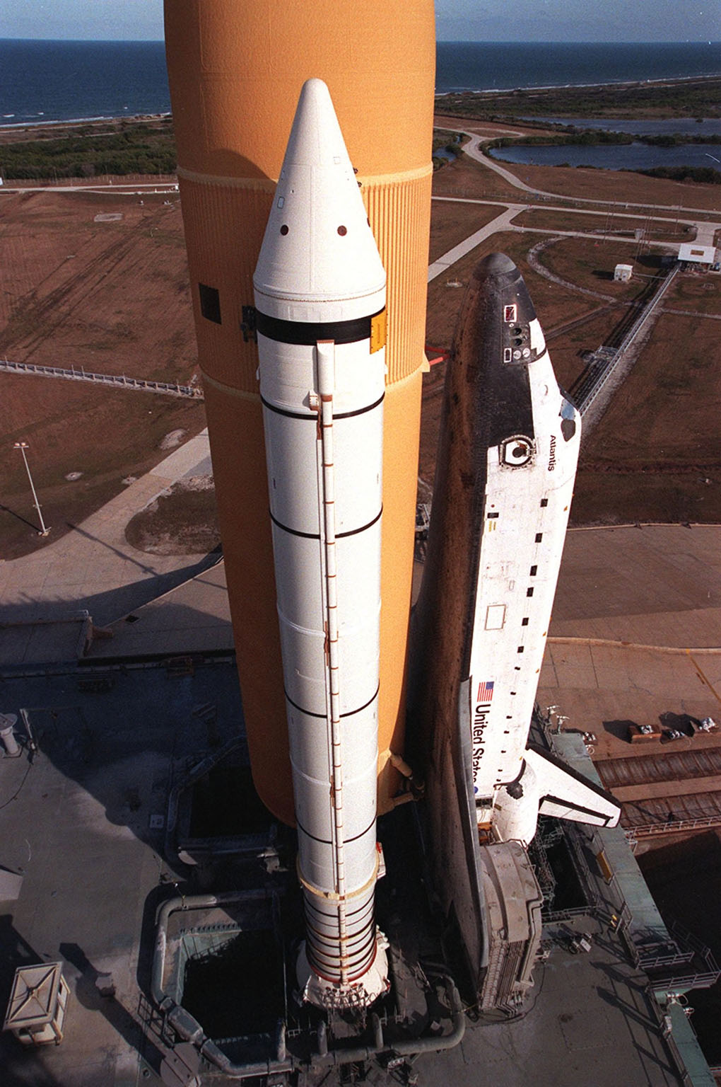 KENNEDY SPACE CENTER, Fla. -- Resting atop the Mobile Launcher Platform, Space Shuttle Atlantis is viewed from a high level on the Fixed Service Structure. Seen is one of its solid rocket boosters and the external tank. Next to the wing of the orbiter is one of two tail service masts, which support the fluid, gas and electrical requirements of the orbiter?s liquid oxygen and liquid hydrogen aft T-0 umbilicals. On the horizon is the Atlantic Ocean. Atlantis will fly on mission STS-98, the seventh construction flight to the International Space Station, carrying the U.S. Laboratory, named Destiny. The lab has five system racks already installed inside the module. After delivery of electronics in the lab, electrically powered attitude control for Control Moment Gyroscopes will be activated. Atlantis is scheduled for launch no earlier than Jan. 19, 2001, with a crew of five