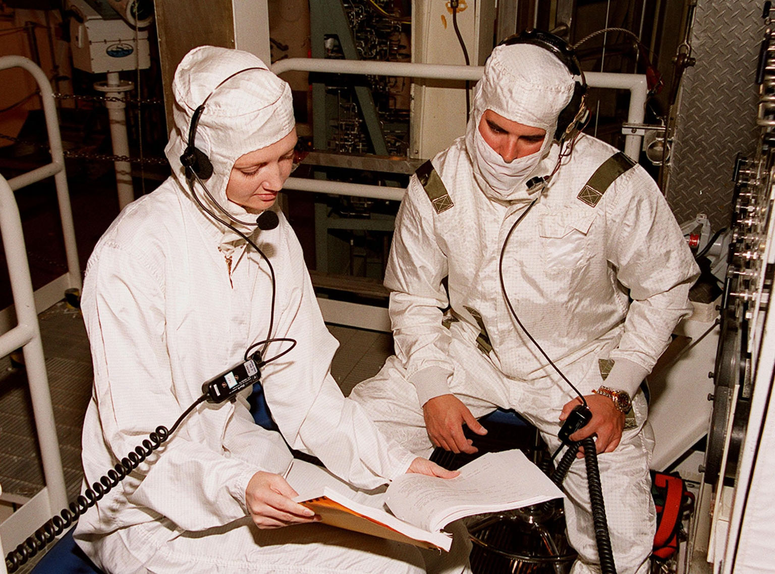 KENNEDY SPACE CENTER, FLA. -- In the Payload Changeout Room at Launch Pad 39A, technicians read a manual on the Payload Ground-Handling Mechanism hook instrumentation unit. The PGHM will be used in moving the U.S. Lab Destiny out of the payload canister and into the PCR. Destiny will then be transferred to the payload bay of Atlantis for mission STS-98. A key element in the construction of the International Space Station, Destiny is designed for space science experiments. STS-98 is the seventh construction flight to the ISS. Launch of STS-98 is scheduled for Jan. 19 at 2:11 a.m. EST