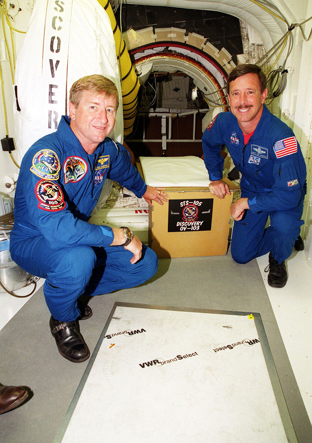 KENNEDY SPACE CENTER, Fla. -- Expedition Three Commander Frank Culbertson (left) and STS-105 Commander Scott Horowitz (right), in the White Room at Launch Pad 39A, have placed the mission sign at the entrance into Space Shuttle Discovery. Both crews are at KSC to take part in Terminal Countdown Demonstration Test activities, which include emergency egress training, a simulated launch countdown and familiarization with the payload. Mission STS-105 will be transporting the Expedition Three crew, several payloads and scientific experiments to the International Space Station aboard Discovery. The current Expedition Two crew members on the Station will return to Earth on Discovery. Launch of Discovery is scheduled no earlier than Aug. 9, 2001