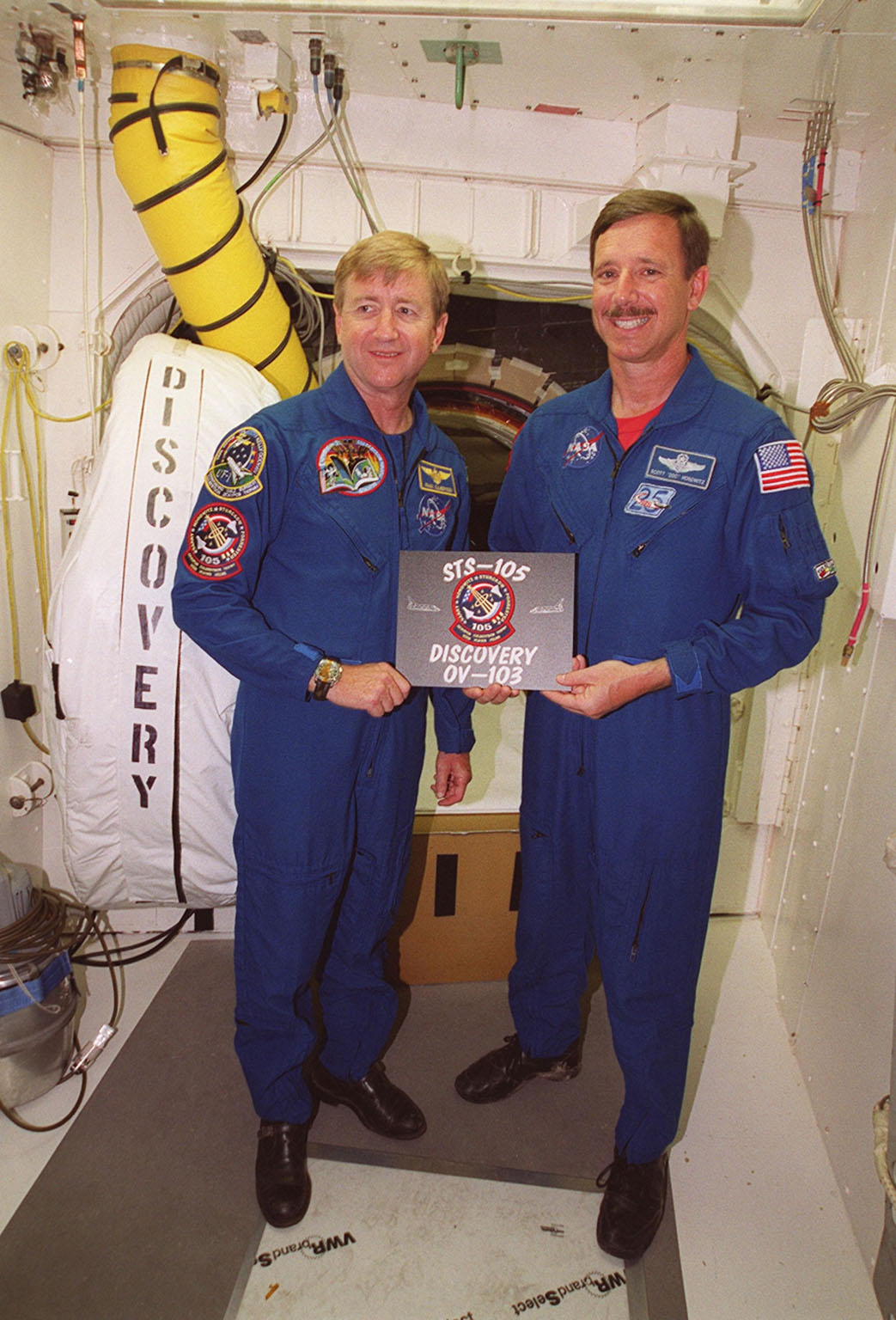 KENNEDY SPACE CENTER, Fla. -- Expedition Three Commander Frank Culbertson (left) and STS-105 Commander Scott Horowitz (right), in the White Room at Launch Pad 39A, hold the sign for their mission. Both crews are at KSC to take part in Terminal Countdown Demonstration Test activities, which include emergency egress training, a simulated launch countdown and familiarization with the payload. Mission STS-105 will be transporting the Expedition Three crew, several payloads and scientific experiments to the International Space Station aboard Discovery. The current Expedition Two crew members on the Station will return to Earth on Discovery. Launch of Discovery is scheduled no earlier than Aug. 9, 2001