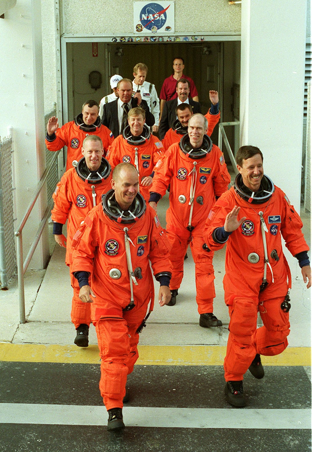 KENNEDY SPACE CENTER, Fla. -- The STS-105 and Expedition Three crews exit the Operations and Checkout Building on their way to Launch Pad 39A and a simulated launch countdown. From front to back, the crew members are Pilot Rick Sturckow (left) and Commander Scott Horowitz (right); Mission Specialists Patrick Forrester (left) and Dan Barry (right); cosmonaut Vladimir Nikolaevich Dezhurov (left), Commander Frank Culbertson (center) and cosmonaut Mikhail Tyurin (right). Both crews are at Kennedy Space Center participating in a Terminal Countdown Demonstration Test, a dress rehearsal for launch. The activities also include emergency egress training and familiarization with the payload. Mission STS-105 will be transporting the Expedition Three crew, several payloads and scientific experiments to the International Space Station aboard Space Shuttle Discovery. The Expedition Two crew members currently on the Station will return to Earth on Discovery. The mission is scheduled to launch no earlier than Aug. 9, 2001