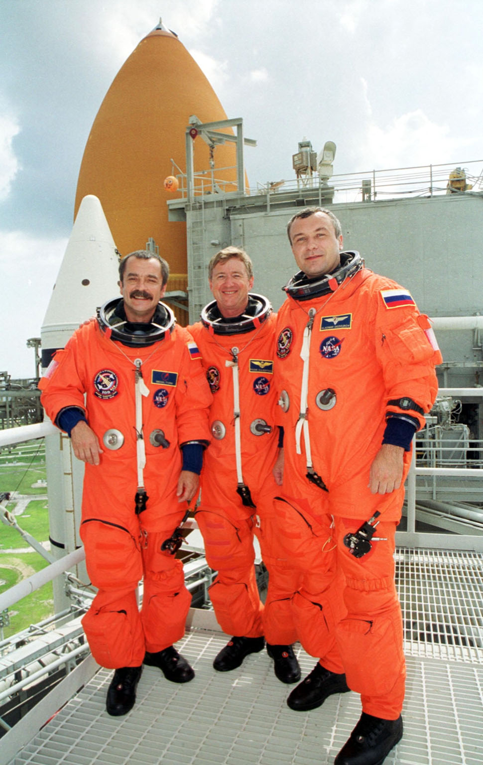 KENNEDY SPACE CENTER, Fla. -- The Expedition Three crew poses on the Fixed Service Structure at Launch Pad 39A. From left are cosmonaut Mikhail Tyurin, commander Frank Culbertson and cosmonaut Vladimir Nikolaevich Dezhurov. The STS-105 and Expedition Three crews are at Kennedy Space Center participating in a Terminal Countdown Demonstration Test, a dress rehearsal for launch. The activities include emergency egress training, a simulated launch countdown and familiarization with the payload. Mission STS-105 will be transporting the Expedition Three crew, several payloads and scientific experiments to the International Space Station aboard Space Shuttle Discovery. The Expedition Two crew members currently on the Station will return to Earth on Discovery. The mission is scheduled to launch no earlier than Aug. 9, 2001
