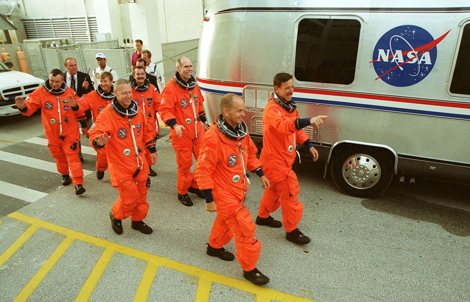 KENNEDY SPACE CENTER, Fla. -- The STS-105 and Expedition Three crews wave to onlookers as they head for the Astrovan to take them to Launch Pad 39A and a simulated launch countdown. From left to right are cosmonaut Vladimir Nikolaevich Dezhurov, Commander Frank Culbertson and cosmonaut Mikhail Tyurin. Ahead of them are Mission Specialists Patrick Forrester and Dan Barry, Pilot Rick Sturckow and Commander Scott Horowitz. Both crews are at Kennedy Space Center participating in a Terminal Countdown Demonstration Test, a dress rehearsal for launch. The activities also include emergency egress training and familiarization with the payload. Mission STS-105 will be transporting the Expedition Three crew, several payloads and scientific experiments to the International Space Station aboard Space Shuttle Discovery. The Expedition Two crew members currently on the Station will return to Earth on Discovery. The mission is scheduled to launch no earlier than Aug. 9, 2001
