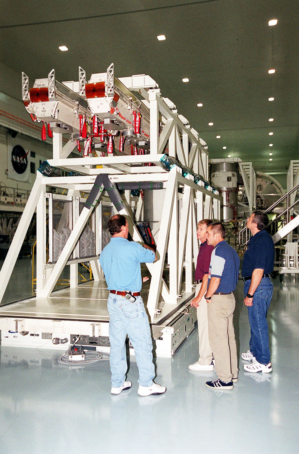 KENNEDY SPACE CENTER, Fla. -- In the Space Station Processing Facility, the Expedition Three crew (right) listen to a worker discuss solar panels seen here on a workstand. The crew members are (left to right) Commander Frank Culbertson and cosmonauts Mikhail Tyurin and Vladimir Dezhurov. The STS-105 payload includes the Early Ammonia Servicer (EAS), Multi-Purpose Logistics Module Leonardo and various experiments attached on the port and starboard adapter beams. The EAS contains spare ammonia for the Station?s cooling system. Ammonia is the fluid used in the radiators that cool the Station?s electronics. The EAS will be installed on the P6 truss holding the giant U.S. solar arrays, batteries and cooling radiators. Leonardo is filled with laboratory racks of science equipment and racks and platforms of experiments and supplies. Discovery is scheduled to be launched Aug. 9, 2001