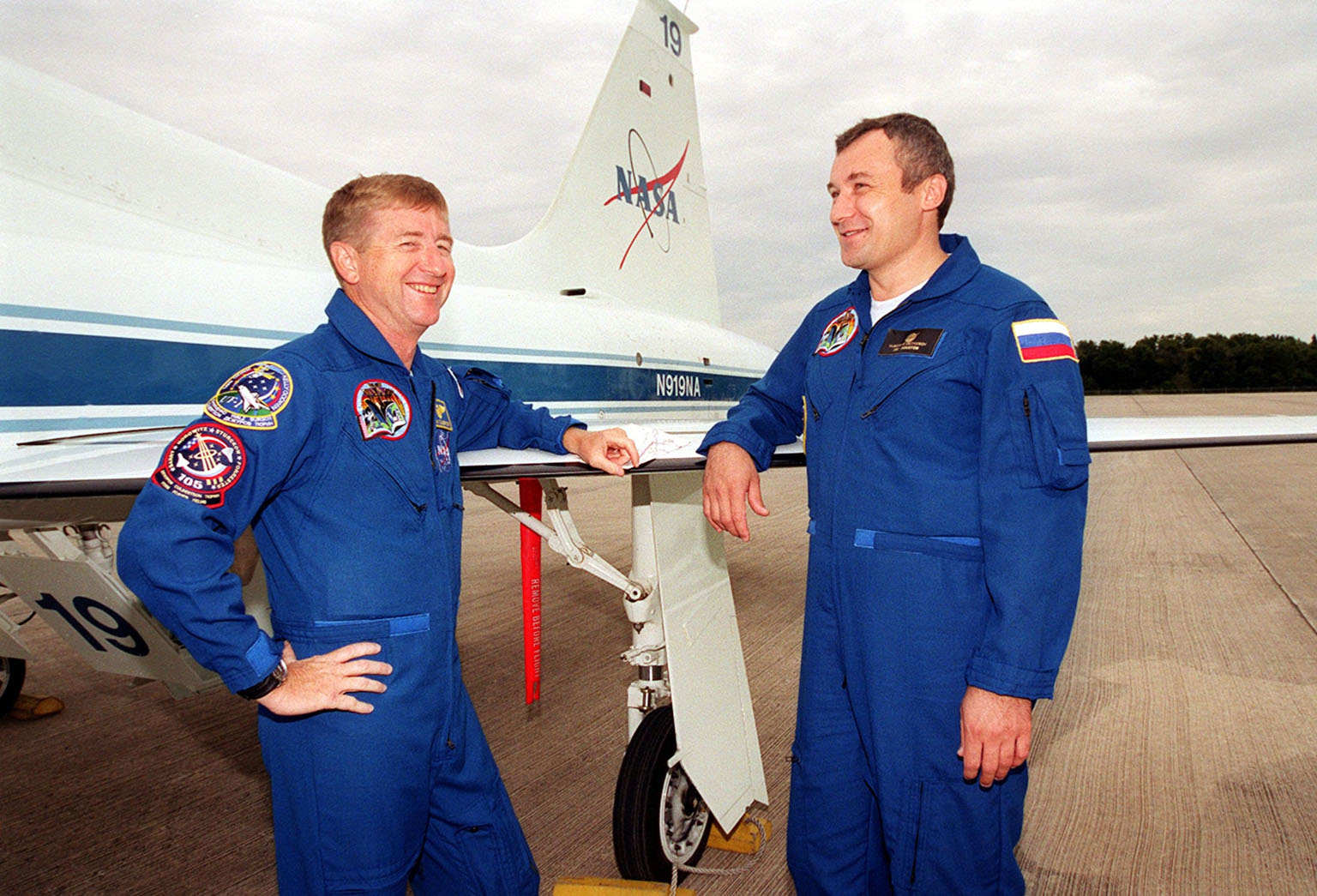 KENNEDY SPACE CENTER, Fla. -- Expedition Three crew members Commander Frank Culbertson (left) and cosmonaut Vladimir Dezhurov (right) wait by a T-38 jet for their morning training flights. The Expedition Three and STS-105 crews are preparing for launch on Aug. 9. On mission STS-105, Discovery will be transporting the Expedition Three crew and several payloads and scientific experiments to the Space Station. The Early Ammonia Servicer (EAS) tank, which contains spare ammonia for the Station?s cooling system and will support the thermal control subsystems until a permanent system is activated, will be attached to the Station during two spacewalks. The three-member Expedition Two crew will be returning to Earth aboard Discovery after a five-month stay on the Station