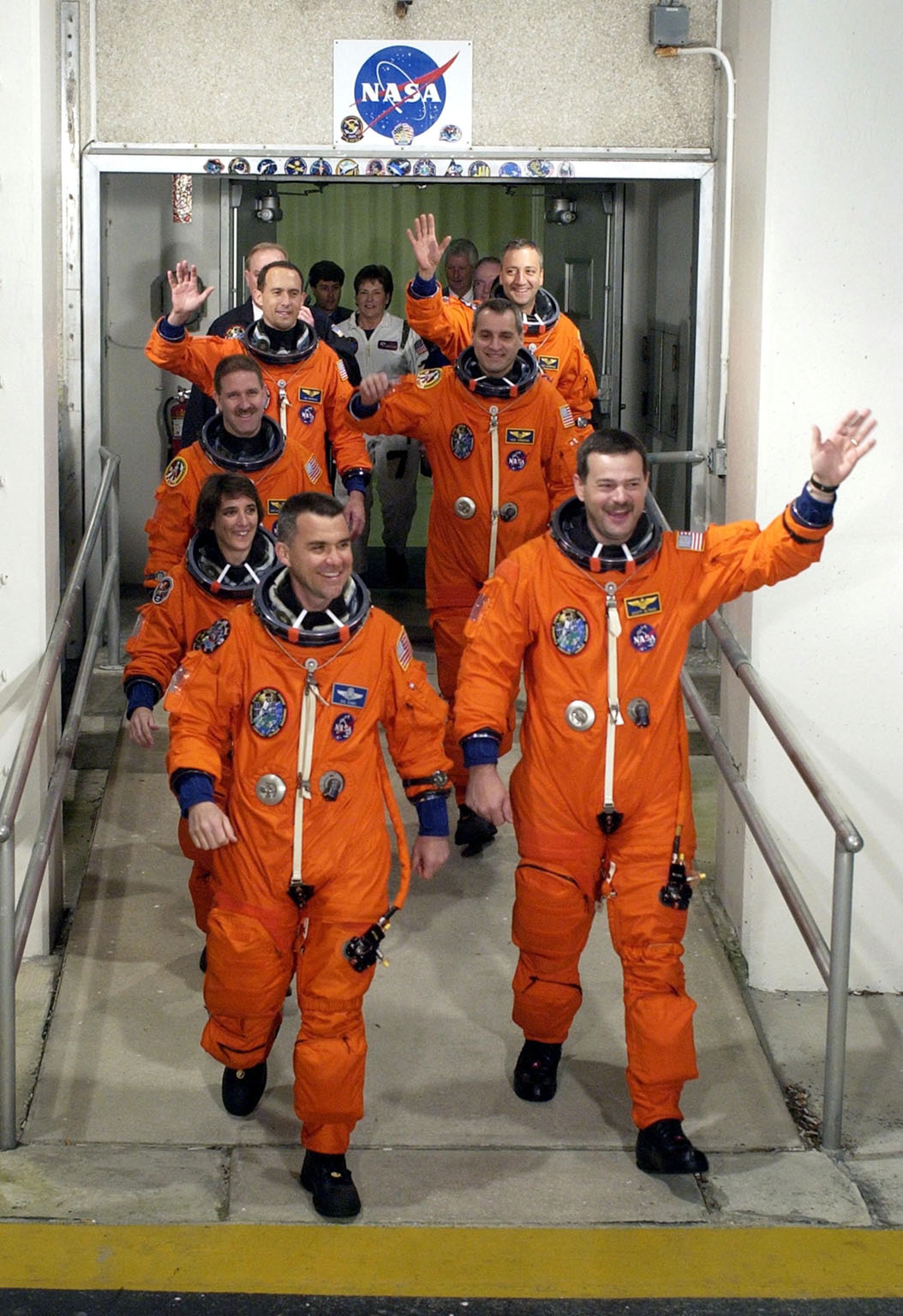 KENNEDY SPACE CENTER, Fla. - The STS-109 crew members wave to onlookers as they stride out from the Operations and Checkout Building, eager to get to the launch pad. They are, from front to back, Pilot Duane G. Carey (left) and Commander Scott D. Altman (right); Mission Specialist Nance Jane Currie; Payload Commander John M. Grunsfeld (left) and Richard M. Linnehan (right); James H. Newman (left) and Michael J. Massimino (right). On mission STS-109, the crew will capture the Hubble Space Telescope using the Shuttle's robotic arm and secure it on a workstand in Columbia's payload bay. Four mission specialists will perform five scheduled spacewalks to complete system upgrades to the telescope. More durable solar arrays, a large gyroscopic assembly to help point the telescope properly, a new telescope power control unit, and a cooling system to restore the use of a key infrared camera and spectrometer unit, which has been dormant since 1999, will all be installed. In addition, the telescope's view of the Universe will be improved with the addition of the Advanced Camera for Surveys (ACS), which replaces the Faint Object Camera, the last of Hubble's original instruments. Mission STS-109 is the 27th flight of the orbiter Columbia and the 108th flight overall in NASA's Space Shuttle program. After the 11-day mission, STS-109 is scheduled to land about 4:35 a.m. EST on March 12. [Photo by Scott Andrews