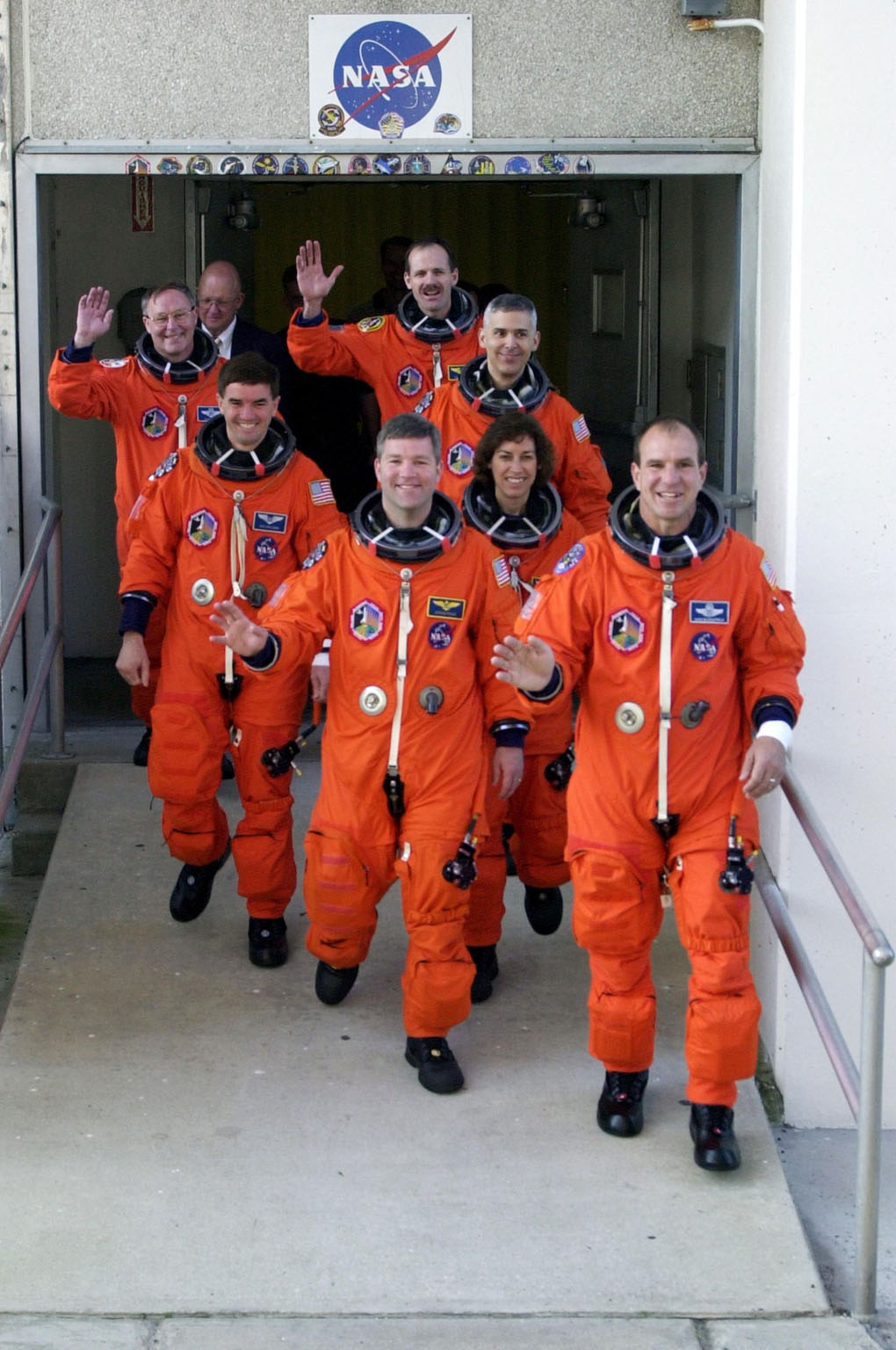 KENNEDY SPACE CENTER, FLA. -- The STS-110 crew walks out of the Operations and Checkout Building on their way to the launch pad for a simulated launch countdown. From the rear, left row, are Mission Specialists Jerry Ross and Rex Walheim, Pilot Stephen Frick; right row, Mission Specialists Steven Smith, Lee Morin and Ellen Ocho, and Commander Michael Bloomfield. The simulation is part of Terminal Countdown Demonstration Test activities. TCDT also includes emergency egress training and is held at KSC prior to each Space Shuttle flight. Scheduled for launch April 4, the 11-day mission will feature Shuttle Atlantis docking with the International Space Station (ISS) and delivering the S0 truss, the centerpiece-segment of the primary truss structure that will eventually extend over 300 feet