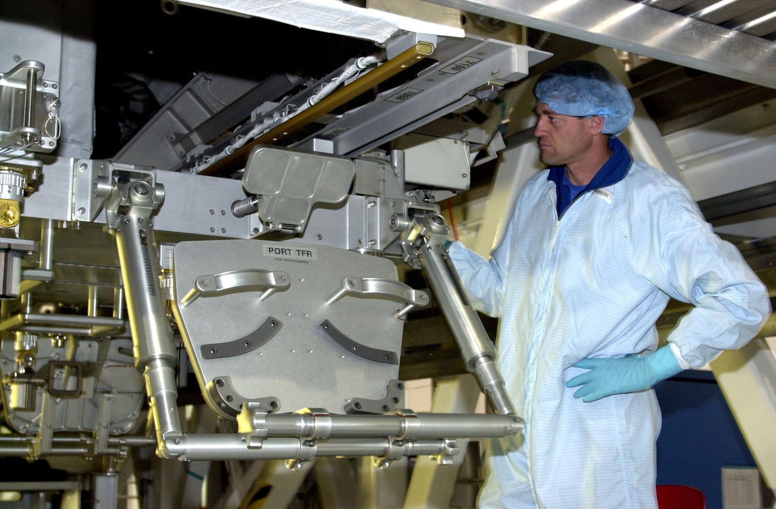 KENNEDY SPACE CENTER, FLA. -- In the Space Station Processing Facility, as part of the Crew Equipment Interface Test, STS-112 Commander Jeffrey Ashby looks over the S1 Integrated Truss Structure, part of the payload for the mission to the International Space Station. The S1 truss is the first starboard (right-side) truss segment, whose main job is providing structural support for the orbiting research facility's radiator panels that cool the Space Station's complex power system. The S1 truss segment also will house communications systems, external experiment positions and other subsystems. The S1 truss will be attached to the S0 truss. Launch of STS-112 is scheduled for Aug. 22, 2002