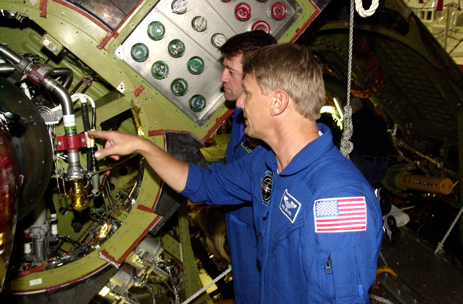 KENNEDY SPACE CENTER, FLA. -- During a Crew Equipment Interface Test, STS-112 Mission Specialist Piers Sellers (foreground) points to an engine line on Atlantis, the designated orbiter for the mission, while Commander Jeffrey Ashby (behind) looks on. STS-112 is the 15th assembly flight to the International Space Station and will be ferrying the S1 Integrated Truss Structure. The S1 truss is the first starboard (right-side) truss segment, whose main job is providing structural support for the radiator panels that cool the Space Station's complex power system. The S1 truss segment also will house communications systems, external experiment positions and other subsystems. The S1 truss will be attached to the S0 truss. STS-112 is currently scheduled for launch Aug. 22, 2002