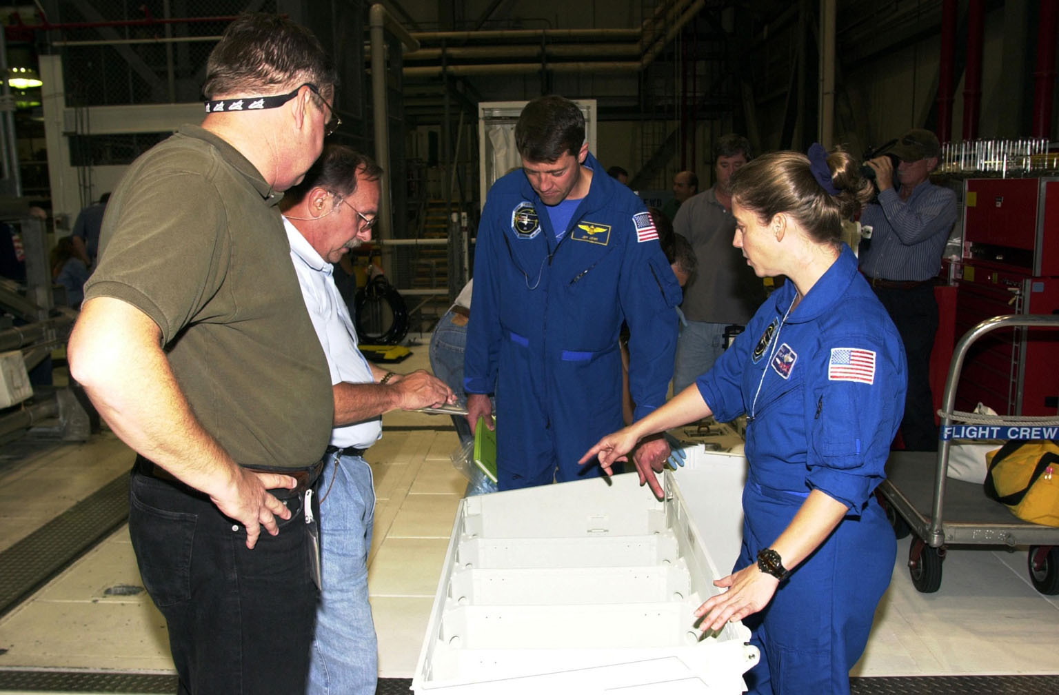 KENNEDY SPACE CENTER, FLA. -- During a Crew Equipment Interface Test, STS-112 Pilot Pamela Melroy (right) points to an area of equipment inventory while Commander Jeffrey Ashby looks on. At left, two technicians help out. STS-112 is the 15th assembly flight to the International Space Station and will be ferrying the S1 Integrated Truss Structure. The S1 truss is the first starboard (right-side) truss segment, whose main job is providing structural support for the radiator panels that cool the Space Station's complex power system. The S1 truss segment also will house communications systems, external experiment positions and other subsystems. The S1 truss will be attached to the S0 truss. STS-112 is currently scheduled for launch Aug. 22, 2002