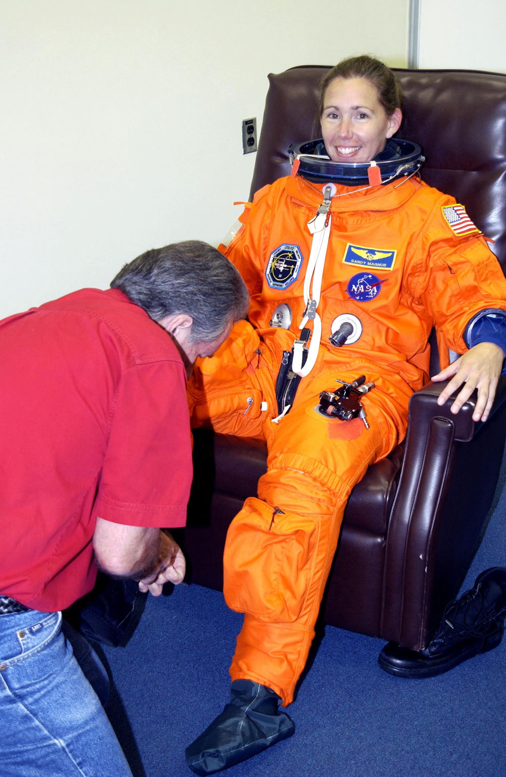 KENNEDY SPACE CENTER, Fla. - STS-112 Mission Specialist Sandra Magnus gets help donning her boots during suit check, part of Terminal Countdown Demonstration Test activities. The TCDT also includes emergency egress training and a simulated launch countdown. The mission aboard Space Shuttle Atlantis is scheduled to launch no earlier than Oct. 2, between 2 and 6 p.m. EDT. STS-112 is the 15th assembly mission to the International Space Station. Atlantis will be carrying the S1 Integrated Truss Structure, the first starboard truss segment. The S1 will be attached to the central truss segment, S0, during the 11-day mission. Magnus will serve as one of two operators of the Canadarm2 robotic arm for S1 truss installation and during three scheduled spacewalks. STS-112 is her first Shuttle flight.