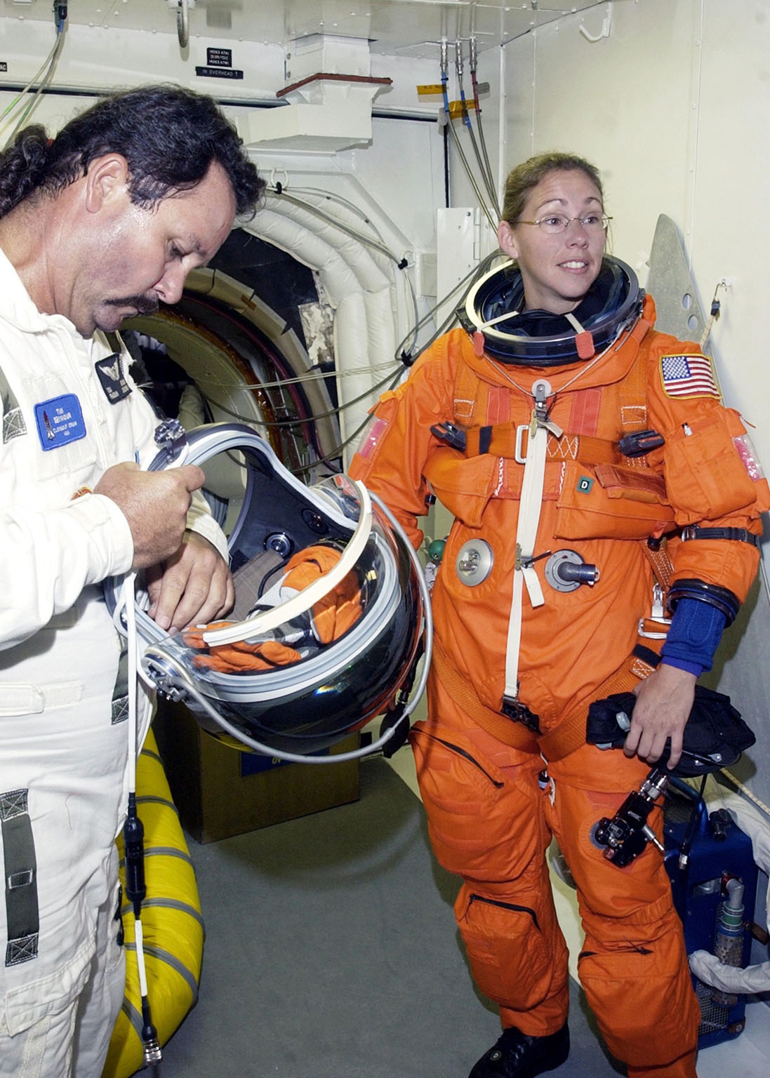 KENNEDY SPACE CENTER, FLA. -- In the White Room at Launch Pad 39B, STS-112 Mission Specialist Sandra Magnus, Ph.D., receives assistance with her spacesuit during a simulated launch countdown, part of Terminal Countdown Demonstration Test activities, a dress rehearsal for launch. Launch of STS-112 aboard Space Shuttle Atlantis is scheduled for Oct. 2, between 2 and 6 p.m. EDT. STS-112 is the 15th assembly mission to the International Space Station. Atlantis will be carrying the S1 Integrated Truss Structure, the first starboard truss segment, which will be attached to the central truss segment, S0, and the Crew and Equipment Translation Aid (CETA) Cart A. The CETA is the first of two human-powered carts that will ride along the ISS railway, providing mobile work platforms for future spacewalking astronauts.