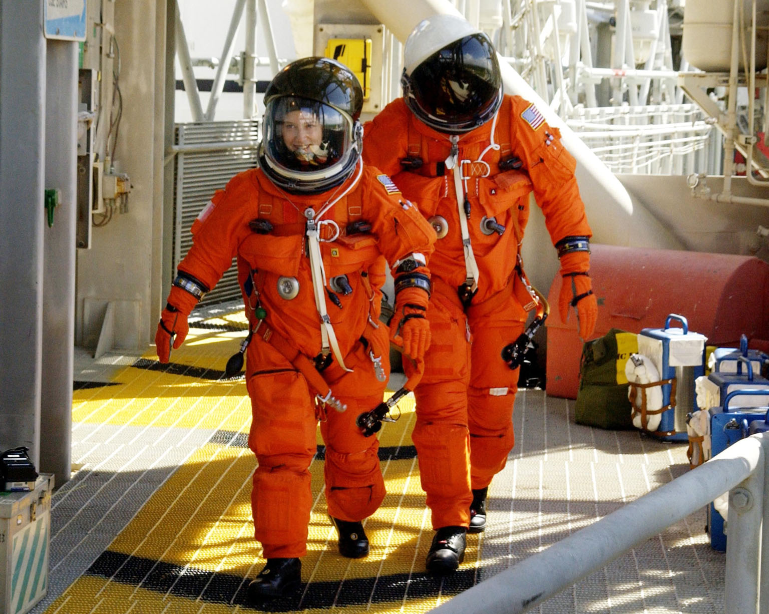 KENNEDY SPACE CENTER, FLA. - STS-112 Pilot Pamela Melroy (left) and Commander Jeffrey Ashby hurry toward the slidewire baskets on the 195-foot level of the Fixed Service Structure, Launch Pad 39B. They and the rest of the crew are practicing emergency egress from the pad during Terminal Countdown Demonstration Test activities. Mission STS-112 aboard Space Shuttle Atlantis is scheduled to launch no earlier than Oct. 2, between 2 and 6 p.m. EDT. STS-112 is the 15th assembly mission to the International Space Station. Atlantis will be carrying the S1 Integrated Truss Structure, the first starboard truss segment, to be attached to the central truss segment, S0, and the Crew and Equipment Translation Aid (CETA) Cart A. The CETA is the first of two human-powered carts that will ride along the ISS railway, providing mobile work platforms for future spacewalking astronauts.