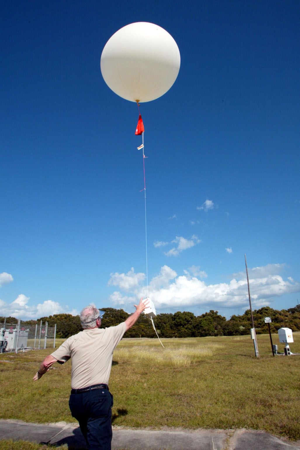 KENNEDY SPACE CENTER, FLA. -- Stephen Ezell, meteorological systems operator at Weather Station A, Cape Canaveral Air Force Station, releases a weather balloon. Such balloons are released twice a day. The package at the bottom is a radio sonde that collects temperature and humidity data as the balloon rises. The data is released to agencies nationwide, including the 45th Space Wing, which uses the data for its daily weather reports. The weather station provides additional data to NASA for launches -- releasing 12 balloons in eight hours prior to liftoff - and landings - releasing 5 balloons in six and a half hours before expected touchdown.
