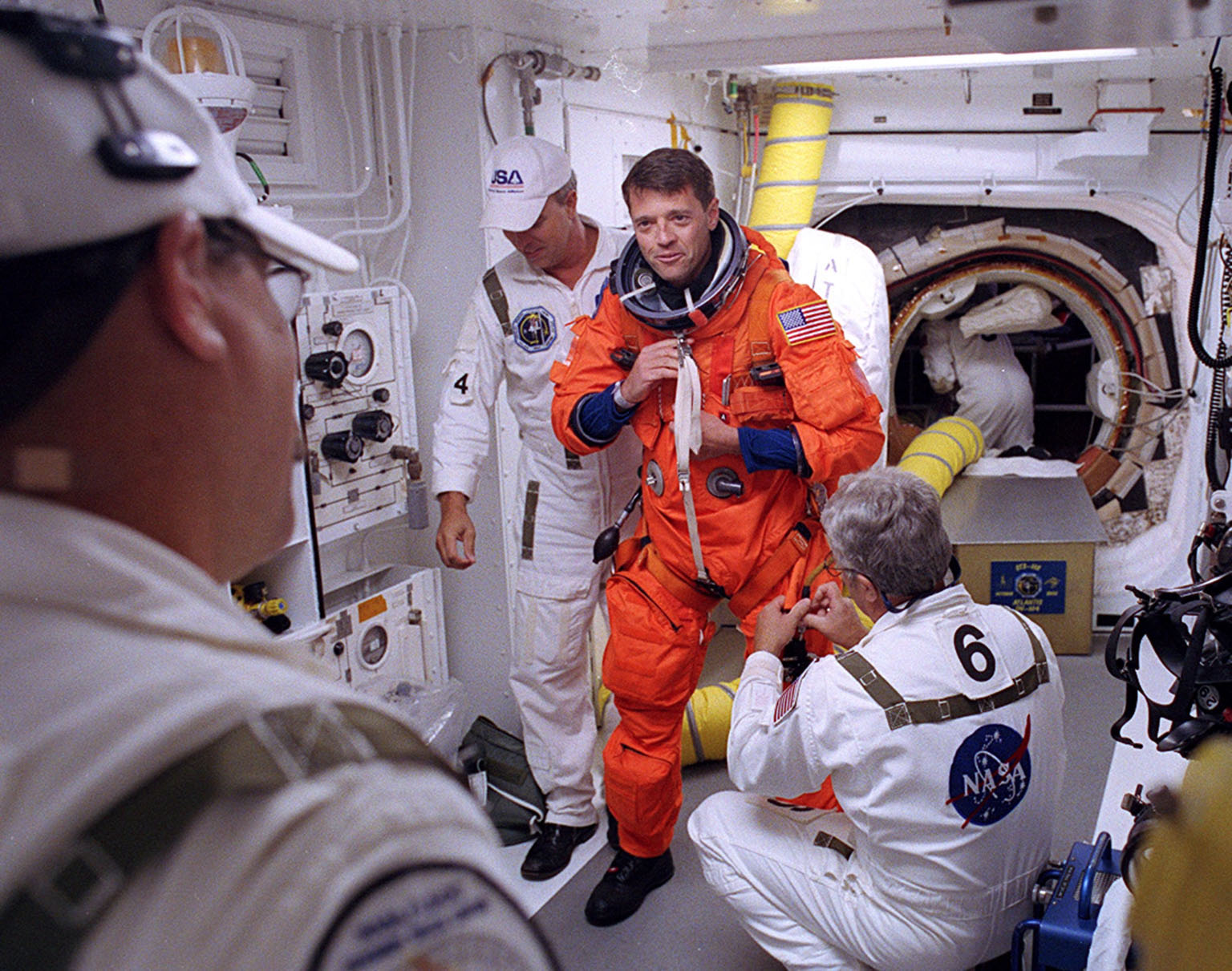 KENNEDY SPACE CENTER, FLA. - -- In the White Room at Launch Pad 39B, STS-112 Commander Jeffrey Ashby receives assistance with his spacesuit before boarding Space Shuttle Atlantis. Liftoff is schedued for 3:46 p.m. EDT. Along with a crew of six, Atlantis will carry the S1 Integrated Truss Structure and the Crew and Equipment Translation Aid (CETA) Cart A to the International Space Station (ISS). The CETA is the first of two human-powered carts that will ride along the ISS railway, providing mobile work platforms for future spacewalking astronauts. On the 11-day mission, three spacewalks are planned to attach the S1 truss.