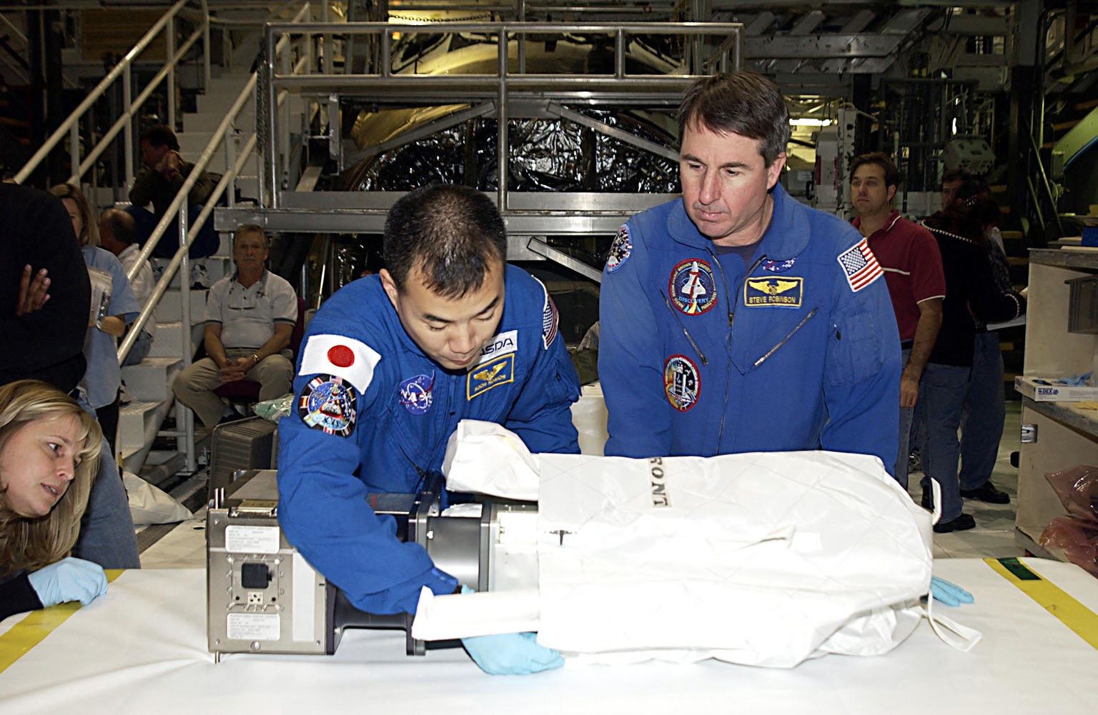 KENNEDY SPACE CENTER, FLA. -- STS-114 Mission Specialist Soichi Noguchi, with the National Space Development Agency of Japan (NASDA), works with equipment as Mission Specialist Stephen K. Robinson, Ph.D., (right) watches. The STS-114 crew is participating in familiarization activities with the hardware that will fly on the mission. STS-114 is a utilization and logistics flight (ULF-1) that will carry Multi-Purpose Logistics Module Raffaello and the External Stowage Platform (ESP-2), as well as the Expedition 7 crew, to the International Space Station. Launch is targeted for March 1, 2003.