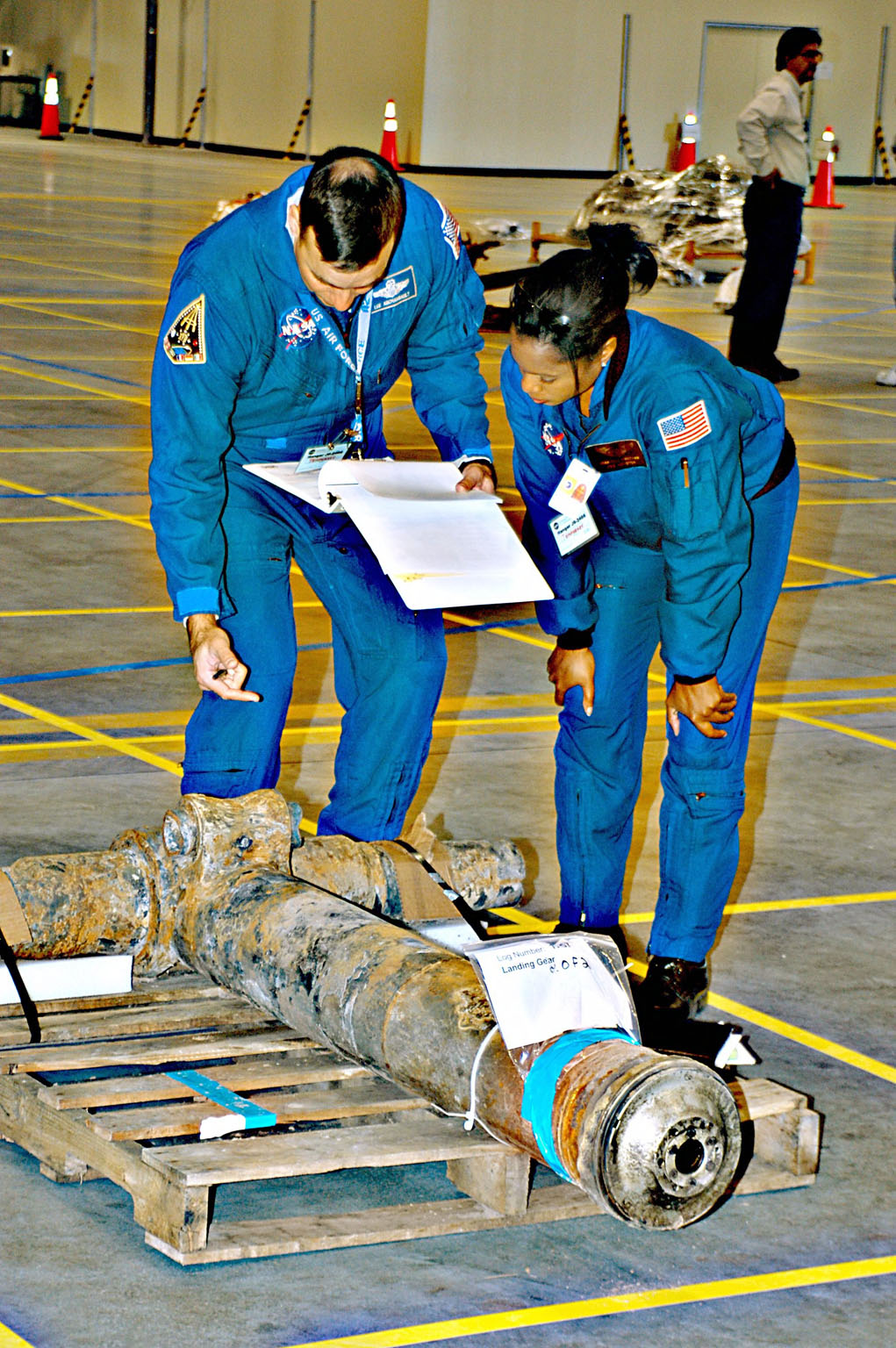 KENNEDY SPACE CENTER, FLA. -- Astronauts Lee Archambault and Joan Higginbotham look at a piece of Columbia debris placed on the grid in the RLV Hangar. The debris was shipped from Barksdale Air Force Base, Shreveport, La. As part of the ongoing investigation into the tragic accident, workers will attempt to reconstruct the orbiter inside the RLV.