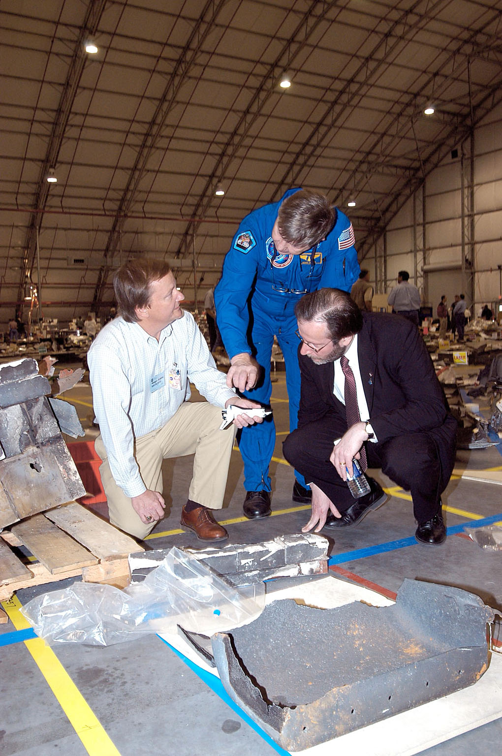 KENNEDY SPACE CENTER, FLA. - In the RLV Hangar at KSC, Shuttle Launch Director Mike Leinbach (left) shows some of the debris from Space Shuttle Columbia to former payload specialist Dr. Roger Crouch (center) and NASA Chief of Staff and White House liaison Courtney Stadd. The search of more than 500,000 acres of primary recovery area for Columbia material has passed the halfway mark. To date about 28 percent of Columbia, by weight, has been delivered to the hangar.