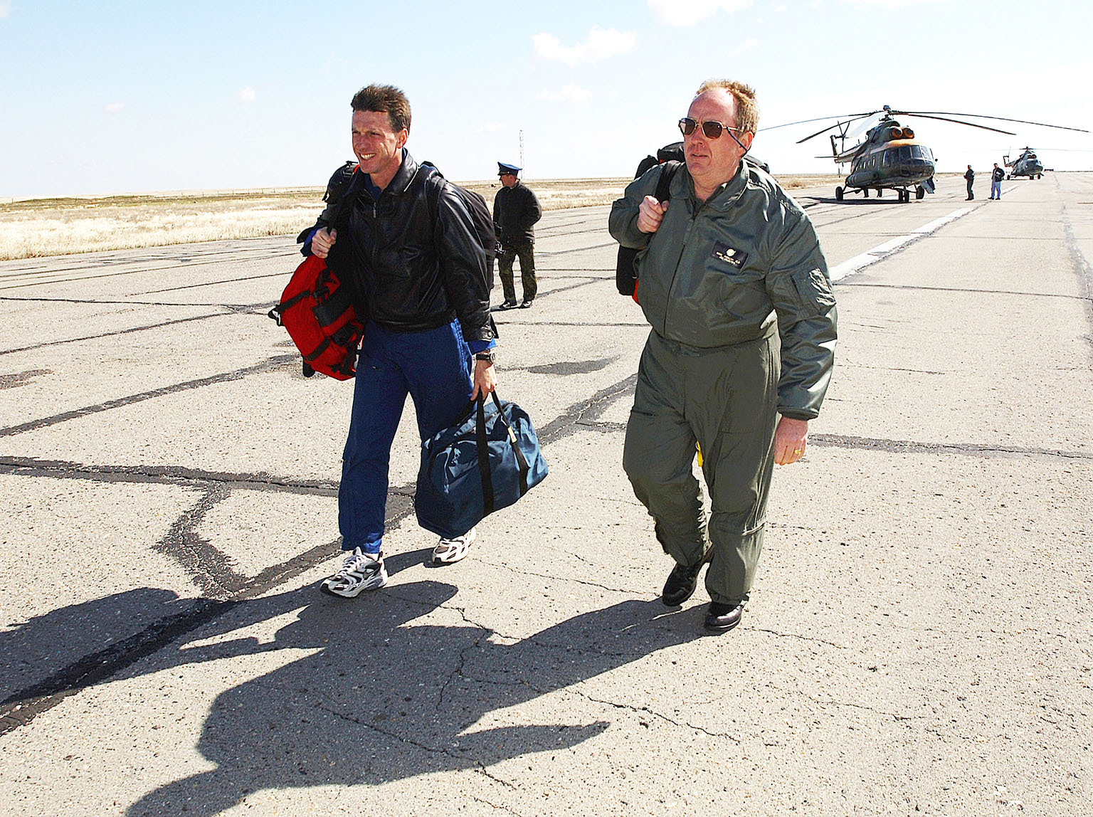KAZAKHSTAN - Astronaut Michael Foale (left) and Mike Duncan (right), Expedition Six lead flight surgeon, move to the lead helicopter after the landing team helicopters needed to return for refueling. Foale and Duncan went on from the refueling to meet the crew of Expedition Six at the landing site. The Expedition Six crew spent 161 days in space, 159 manning the International Space Station. Photo Credit: NASA/Bill Ingalls