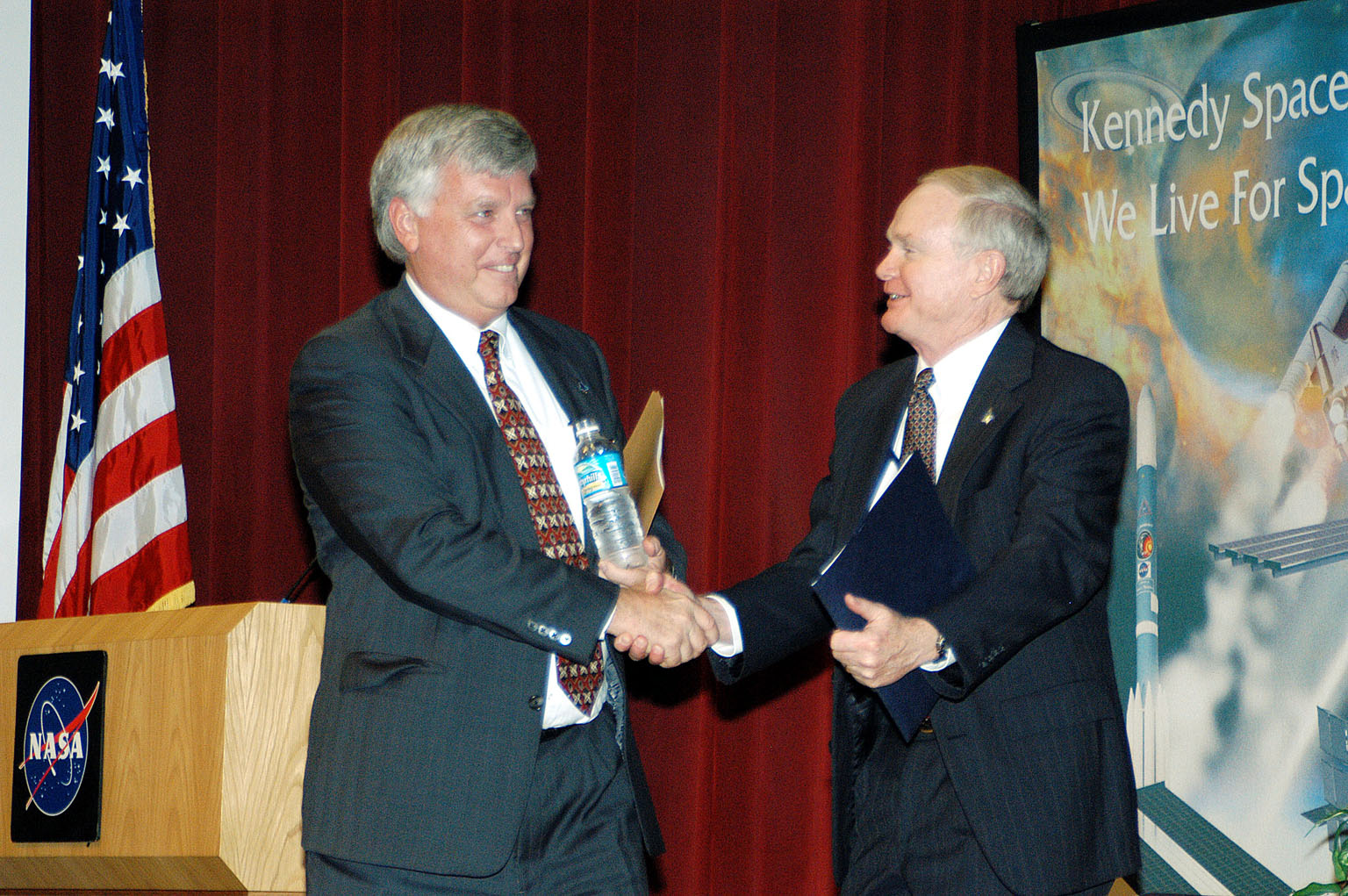 KENNEDY SPACE CENTER, FLA. - KSC Deputy Director James W. Kennedy (left) and KSC Director Roy D. Bridges shake hands before a group of KSC employees assembled in the KSC Training Auditorium. The occasion is the announcement of Kennedy as the next director of the NASA Kennedy Space Center (KSC) in Florida. Kennedy has served as KSC's deputy director since November 2002. He will succeed Bridges, who was appointed on June 13 to lead NASA's Langley Research Center, Hampton, Va.