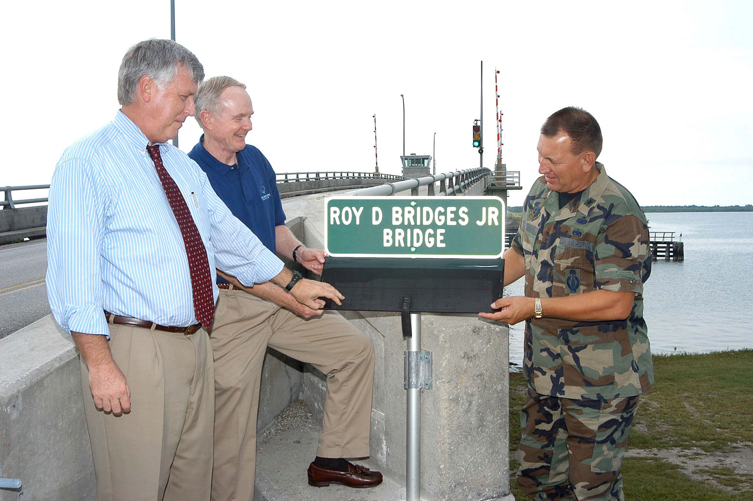 KENNEDY SPACE CENTER, FLA. - Incoming KSC Director James W. Kennedy (left) and departing KSC Director Roy D. Bridges Jr. (center) view the new sign on the NASA Causeway naming the bridge for Bridges who is leaving KSC to become the director of NASA's Langley Research Center, Hampton, Va. At right is the 45th Space Wing Commander Brig. Gen. J. Gregory Pavlovich. The bridge spans the Banana River on the NASA Causeway and connects Kennedy Space Center and Cape Canaveral Air Force Station.