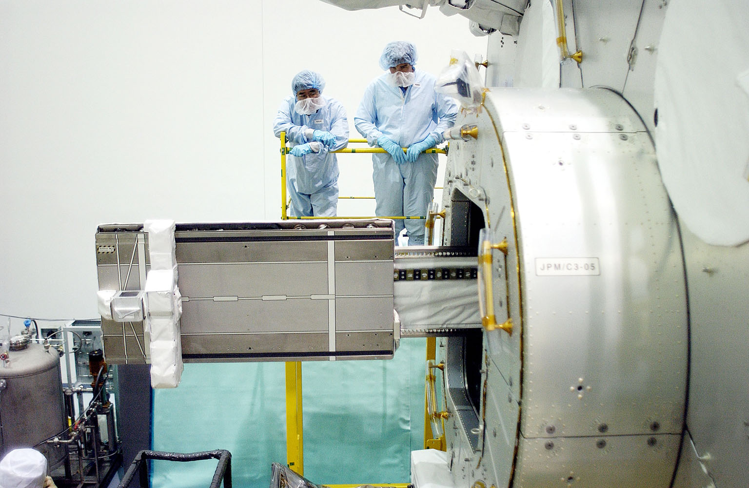 KENNEDY SPACE CENTER, FLA. - In the Space Station Processing Facility, Japanese astronaut Koichi Wakata (top left) and technicians watch as a tray is extended from inside the Pressurized Module, or PM, part of the Japanese Experiment Module (JEM). The PM provides a shirt-sleeve environment in which astronauts on the International Space Station can conduct microgravity experiments. There are a total of 23 racks, including 10 experiment racks, inside the PM providing a power supply, communications, air conditioning, hardware cooling, water control and experiment support functions.