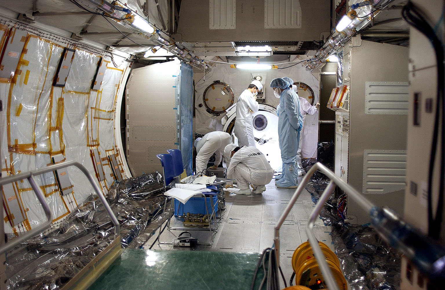 KENNEDY SPACE CENTER, FLA. - In the Space Station Processing Facility, Japanese astronaut Koichi Wakata, dressed in blue protective clothing (at right), looks at the inside of the Pressurized Module, or PM, part of the Japanese Experiment Module (JEM), along with technicians. The PM provides a shirt-sleeve environment in which astronauts on the International Space Station can conduct microgravity experiments. There are a total of 23 racks, including 10 experiment racks, inside the PM providing a power supply, communications, air conditioning, hardware cooling, water control and experiment support functions.