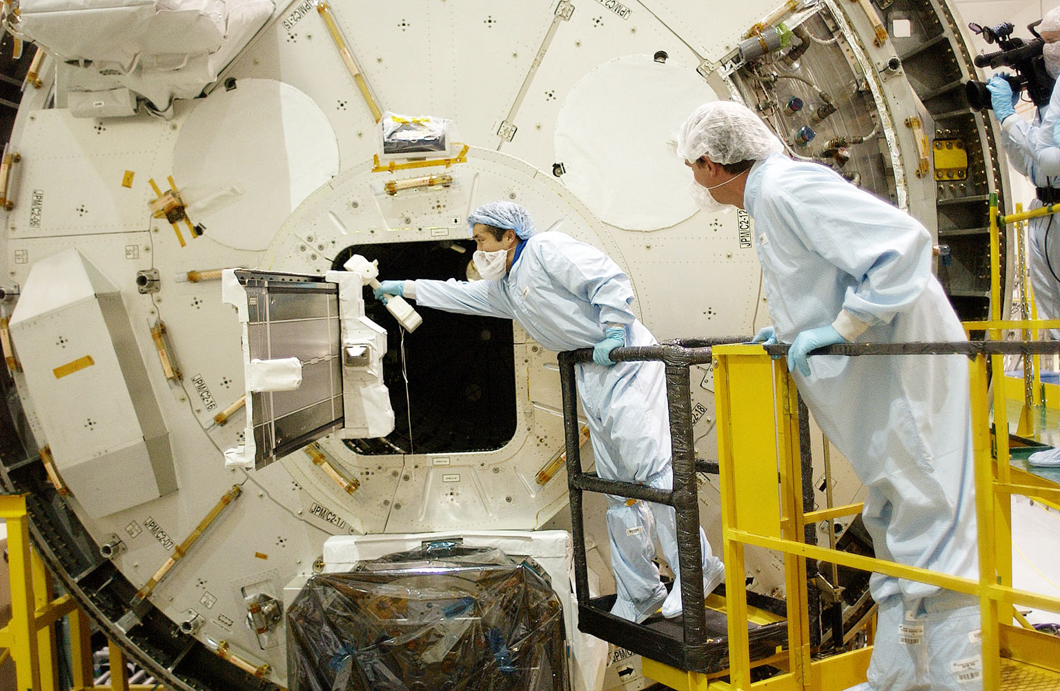 KENNEDY SPACE CENTER, FLA. - Japanese astronaut Koichi Wakata (left) works with a tray extended from inside the Pressurized Module, or PM, part of the Japanese Experiment Module (JEM). The PM provides a shirt-sleeve environment in which astronauts on the International Space Station can conduct microgravity experiments. There are a total of 23 racks, including 10 experiment racks, inside the PM providing a power supply, communications, air conditioning, hardware cooling, water control and experiment support functions.