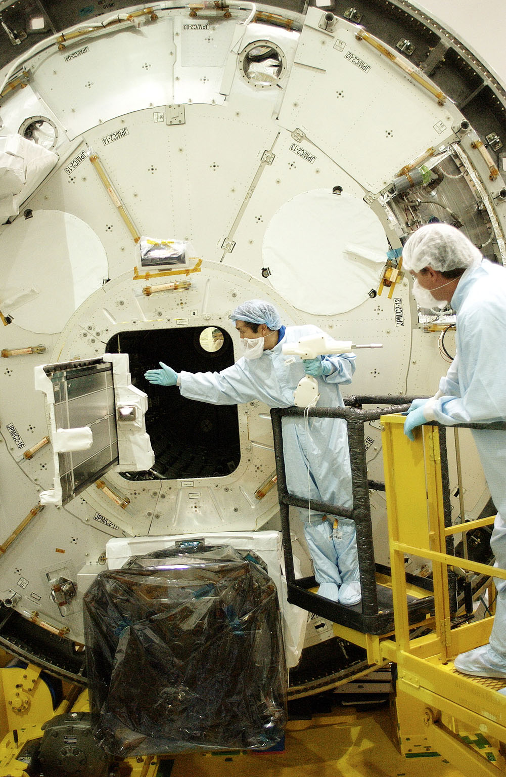 KENNEDY SPACE CENTER, FLA. - Japanese astronaut Koichi Wakata (left) releases a tray extended from inside the Pressurized Module, or PM, that he was working with. Part of the Japanese Experiment Module (JEM), the PM provides a shirt-sleeve environment in which astronauts on the International Space Station can conduct microgravity experiments. There are a total of 23 racks, including 10 experiment racks, inside the PM providing a power supply, communications, air conditioning, hardware cooling, water control and experiment support functions. The JEM/PM is in the Space Station Processing Facility.