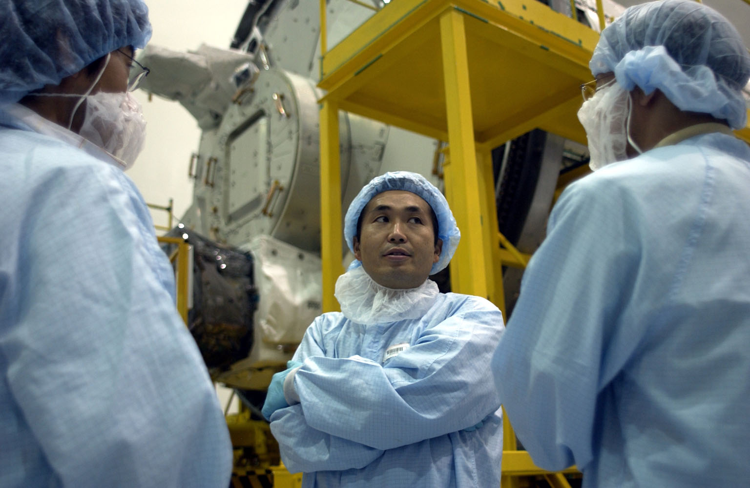 KENNEDY SPACE CENTER, FLA. - In the Space Station Processing Facility, Japanese astronaut Koichi Wakata, dressed in protective clothing, talks with workers before entering the Pressurized Module, or PM, behind him. Part of the Japanese Experiment Module (JEM), the PM provides a shirt-sleeve environment in which astronauts on the International Space Station can conduct microgravity experiments. There are a total of 23 racks, including 10 experiment racks, inside the PM providing a power supply, communications, air conditioning, hardware cooling, water control and experiment support functions.