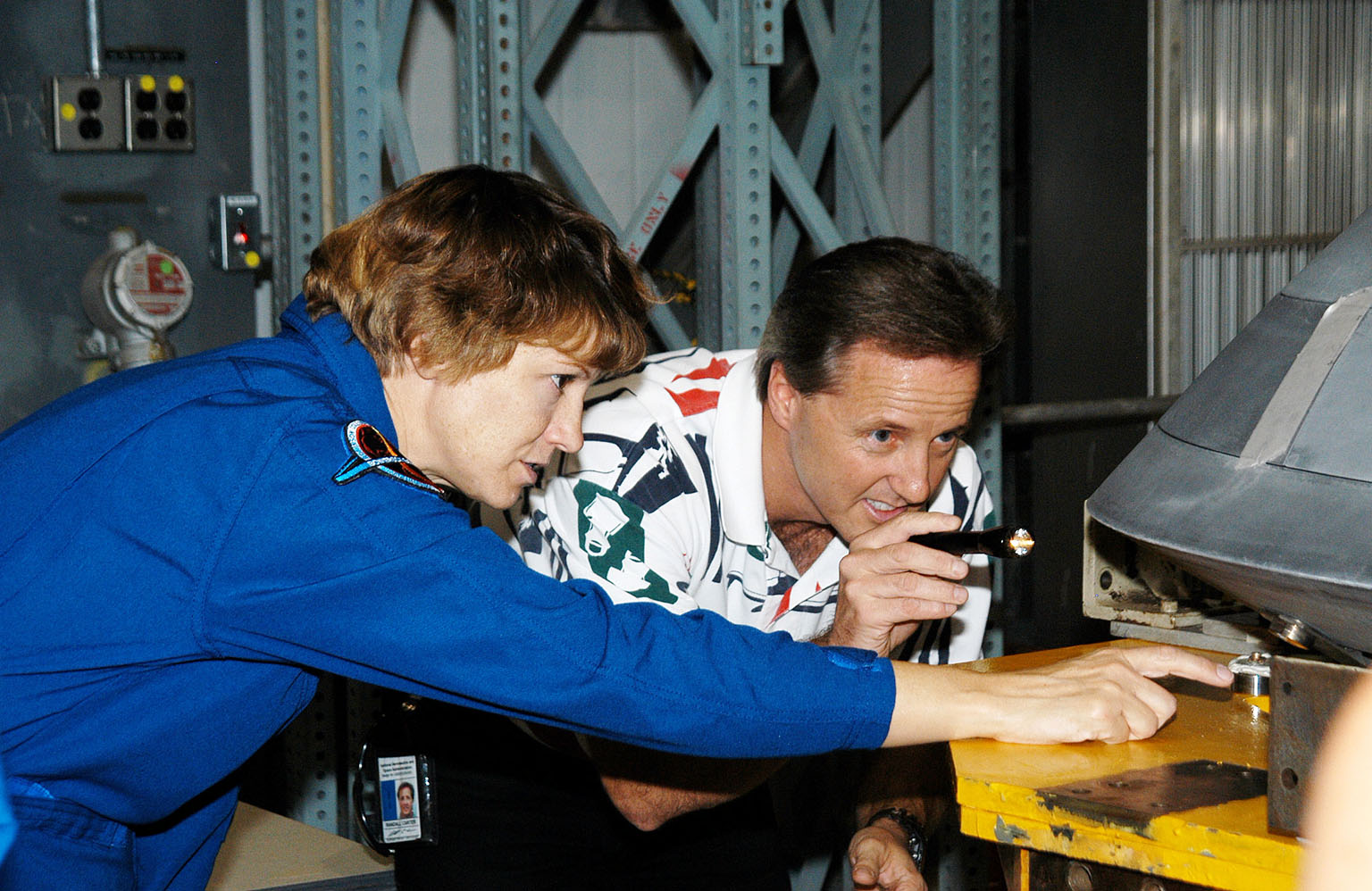 KENNEDY SPACE CENTER, FLA. - In the Orbiter Processing Facility, STS-114 Commander Eileen Collins examines part of the Atlantis nose cap with Randall Carter, who is with The Boeing Company. The nose cap was recently removed from Atlantis. The STS-114 crew is at KSC to take part in crew equipment and orbiter familiarization.