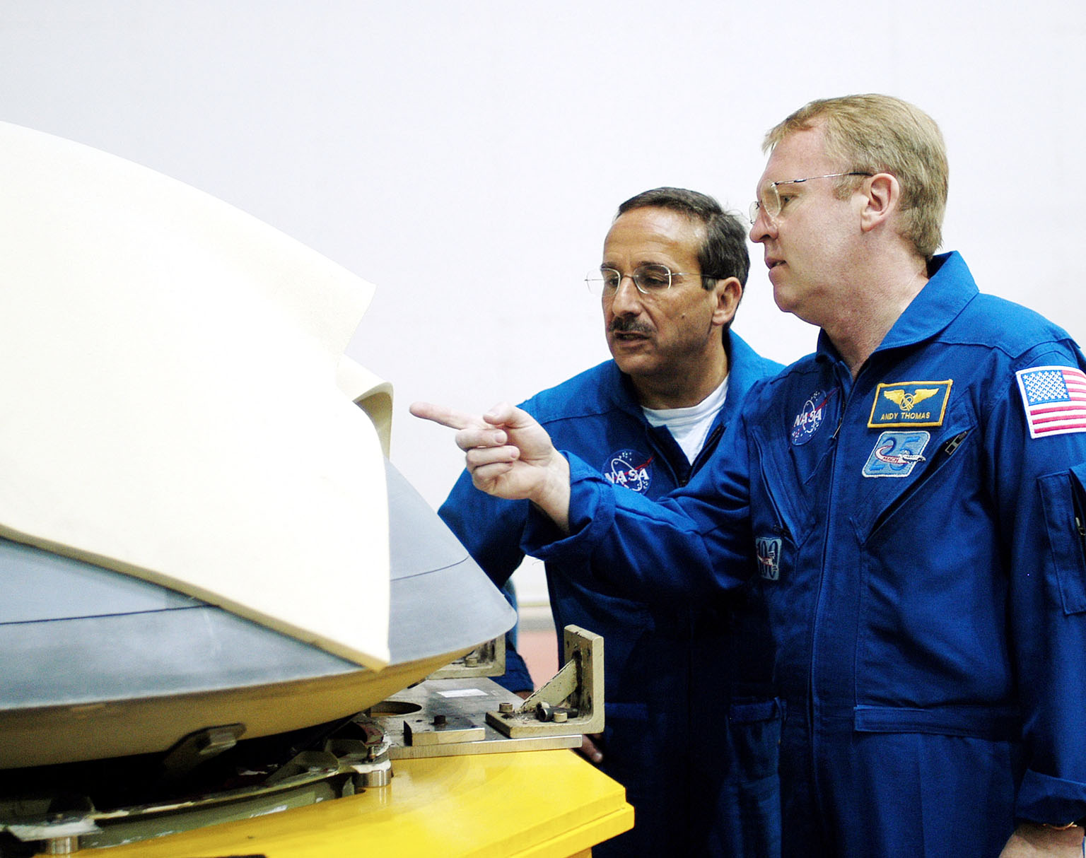 KENNEDY SPACE CENTER, FLA. - In the Orbiter Processing Facility, STS-114 Mission Specialists Charles Camarda and Andy Thomas, who were recently added to the crew, look at the nose cap recently removed from Atlantis. The STS-114 crew is at KSC to take part in crew equipment and orbiter familiarization.