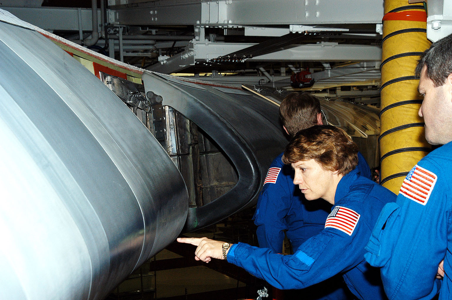 KENNEDY SPACE CENTER, FLA. - In the Orbiter Processing Facility, STS-114 Mission Commander Eileen Collins looks closely at a reinforced carbon-carbon panel on the wing of Atlantis. She and other crew members are at KSC to take part in crew equipment and orbiter familiarization.