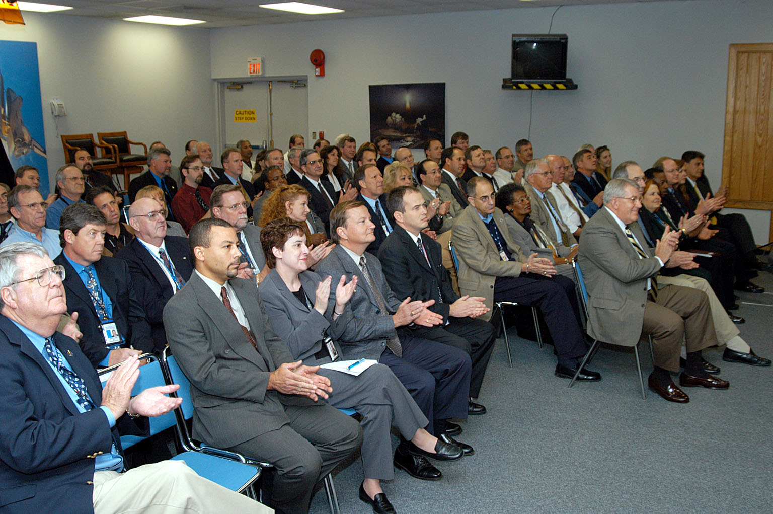 KENNEDY SPACE CENTER, FLA. -- From the KSC television studio, KSC management and other employees applaud President George W. Bush, who addressed the public and an assembly of government officials at NASA Headquarters, outlining a new focus and vision for the space agency. Fourth from left is Mike Leinbach, Shuttle launch director; at right, front row, are Bill Pickavance vice president and associate program manager of Florida Operations, United Space Alliance (USA) and Howard DeCastro, USA vice president and Space Shuttle program manager. The President stated his goals for NASA?s new mission: Completing the International Space Station, retiring the Space Shuttle orbiters, developing a new crew exploration vehicle, and returning to the moon and beyond within the next two decades. Pres. Bush was welcomed by NASA Administrator Sean O?Keefe and Expedition 8 Commander Michael Foale, who greeted him from the International Space Station. Members of the Washington, D.C., audience included astronauts Eileen Collins, Ed Lu and Michael Lopez-Alegria, and former astronaut Gene Cernan.