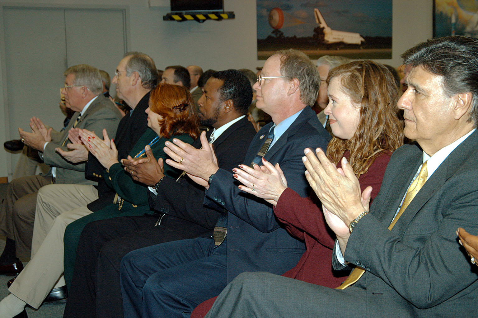 KENNEDY SPACE CENTER, FLA. -- In the KSC television studio, KSC management and other employees applaud President George W. Bush, who addressed the public and an assembly of government officials at NASA Headquarters as he outlined a new focus and vision for the space agency. Seated in the front row, left to right, are Bill Pickavance vice president and associate program manager of Florida Operations, United Space Alliance (USA) ; Howard DeCastro, vice president and Space Shuttle program manager, USA; Shannon Roberts, with External Affairs; Woodrow Whitlow, KSC deputy director; Bruce Buckingham, assistant to Dr. Whitlow; Lisa Malone, director of External Affairs; and Ken Aguilar, chief, Equal Opportunity office. The President stated his goals for NASA?s new mission: Completing the International Space Station, retiring the Space Shuttle orbiters, developing a new crew exploration vehicle, and returning to the moon and beyond within the next two decades. Pres. Bush was welcomed by NASA Administrator Sean O?Keefe and Expedition 8 Commander Michael Foale, who greeted him from the International Space Station. Members of the Washington, D.C., audience included astronauts Eileen Collins, Ed Lu and Michael Lopez-Alegria, and former astronaut Gene Cernan.
