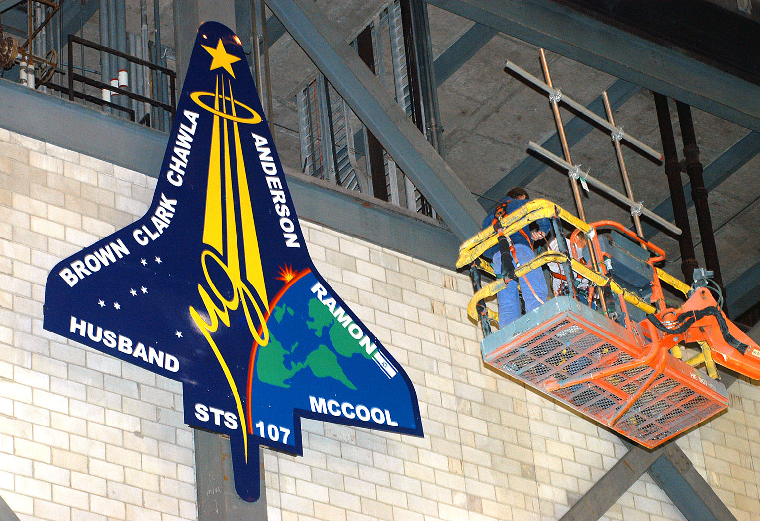 KENNEDY SPACE CENTER, FLA. - Workers install a 20-foot by 15-foot replica of the STS-107 logo above the ?A? on the A tower in the transfer aisle of the Vehicle Assembly Building. The debris from the orbiter Columbia, lost in a tragic accident on its return to Earth from the STS-107 mission, is permanently stored in the tower. A dedication ceremony Jan. 29, 2004, revealed a plaque being installed in the storage area in honor of ?Columbia, the crew of STS-107, and their loved ones.?