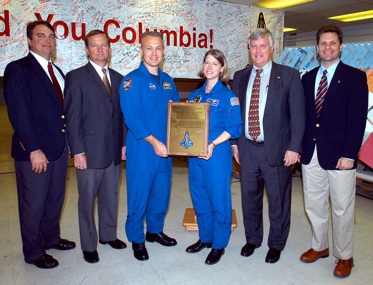 KENNEDY SPACE CENTER, FLA. - Posing with the plaque dedicated to Columbia Jan. 29, 2004, are (left to right) United Space Alliance project leader for Columbia reconstruction Jim Comer, Shuttle Launch Director Mike Leinbach, astronauts Douglas Hurley and Pam Melroy, Center Director Jim Kennedy and NASA Vehicle Manager Scott Thurston. The dedication of the plaque was made in front of the 40-member preservation team in the ?Columbia room,? a permanent repository in the Vehicle Assembly Building of the debris collected in the aftermath of the tragic accident Feb. 1, 2003, that claimed the orbiter and lives of the seven-member crew.