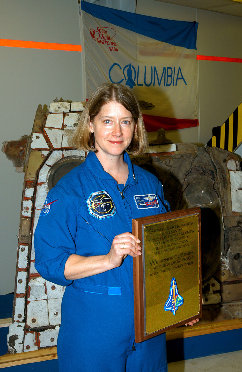 KENNEDY SPACE CENTER, FLA. - Posing with the plaque dedicated to Columbia Jan. 29, 2004, is astronaut Pam Melroy. The dedication ceremony included the 40-member preservation team gathered in the ?Columbia room,? in the Vehicle Assembly Building. The site is a permanent repository of the debris collected in the aftermath of the tragic accident Feb. 1, 2003, that claimed the orbiter and lives of the seven-member crew. Behind Melroy is a piece of the debris.