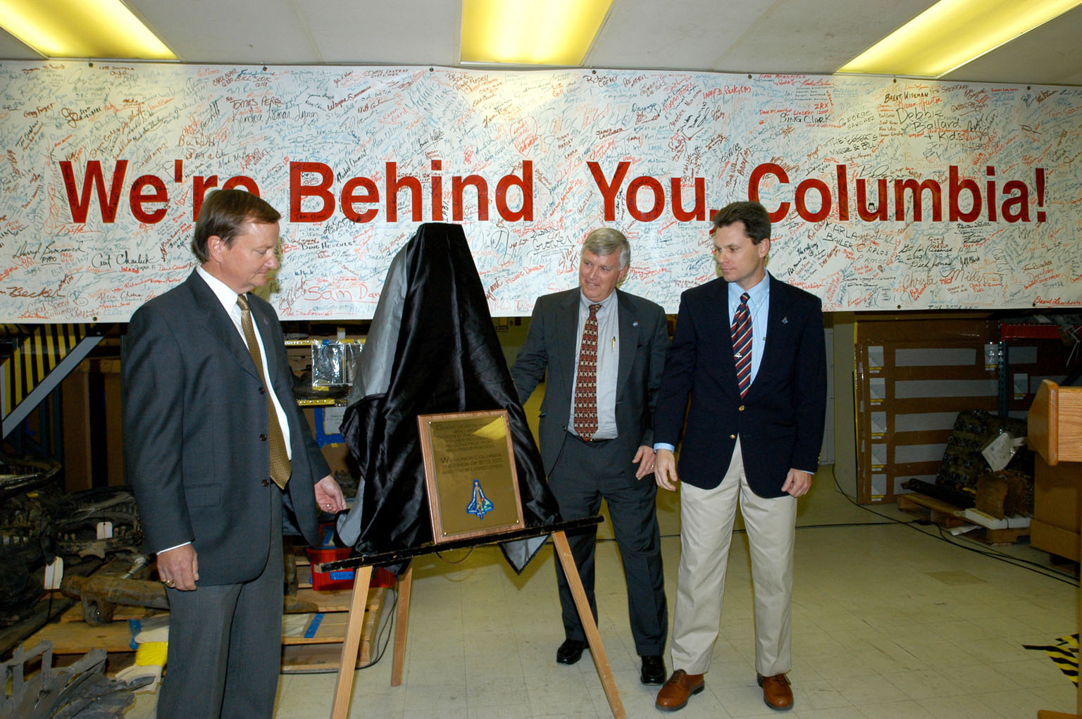 KENNEDY SPACE CENTER, FLA. - In the Vehicle Assembly Building, Shuttle Launch Director Mike Leinbach, Center Director Jim Kennedy and NASA Vehicle Manager Scott Thurston unveil a plaque honoring ?Columbia, the crew of STS-107, and their loved ones.? The site is the ?Columbia room,? a permanent repository of the debris collected in the aftermath of the tragic accident Feb. 1, 2003, that claimed the orbiter and lives of the seven-member crew. The dedication of the plaque was made in front of the 40-member preservation team.
